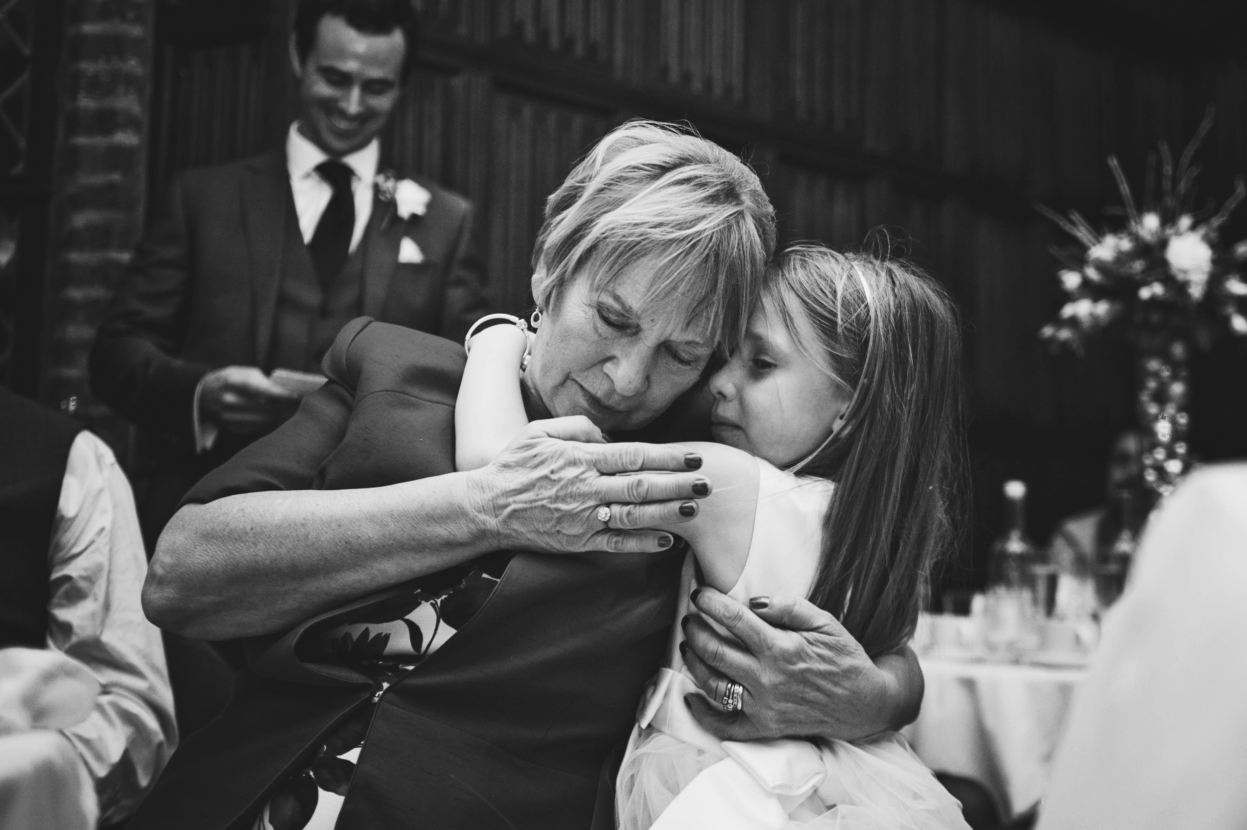 Mother of Bride hugs grand-daughter Leez Priory Christmas Essex UK Documentary Wedding Photographer