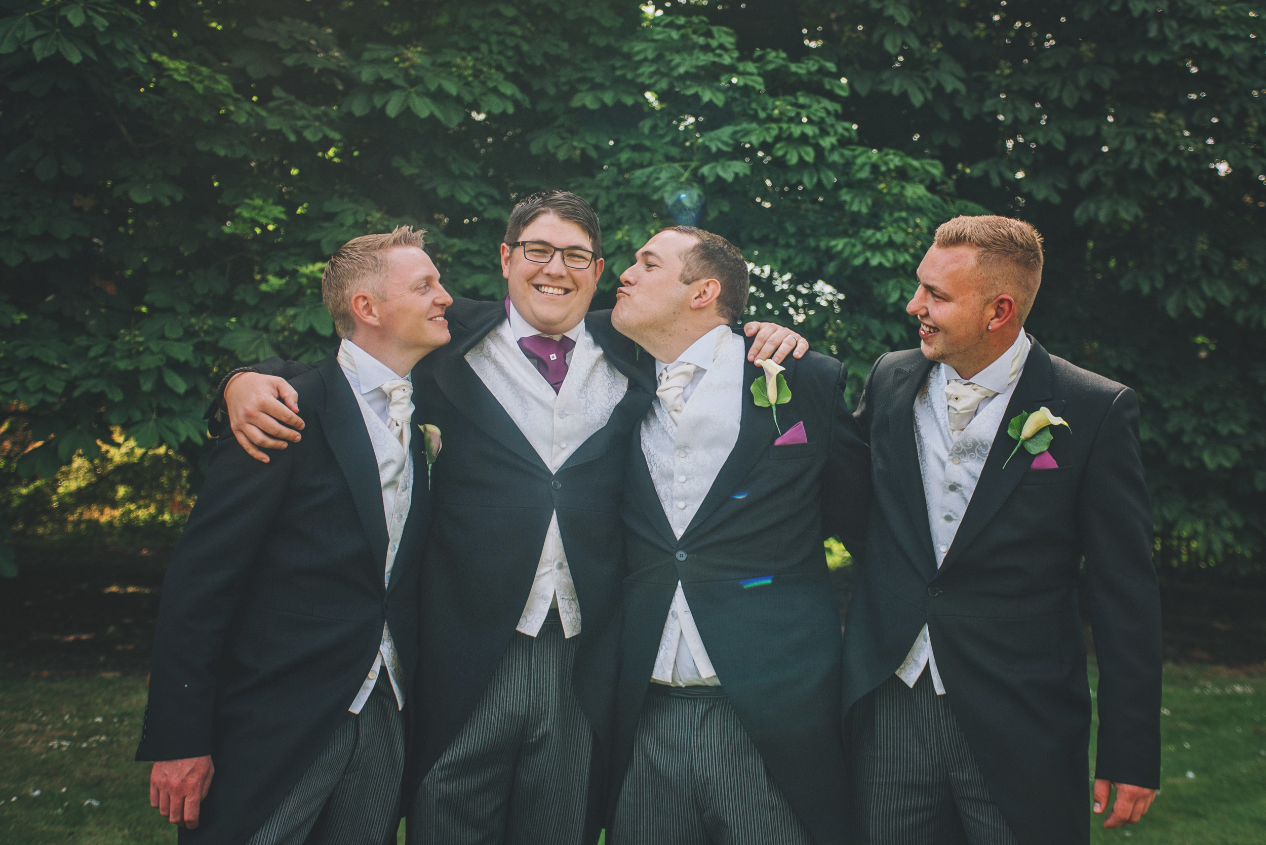 Groomsmen kisses Groom Wood Hall Suffolk Essex UK Documentary Wedding Photographer