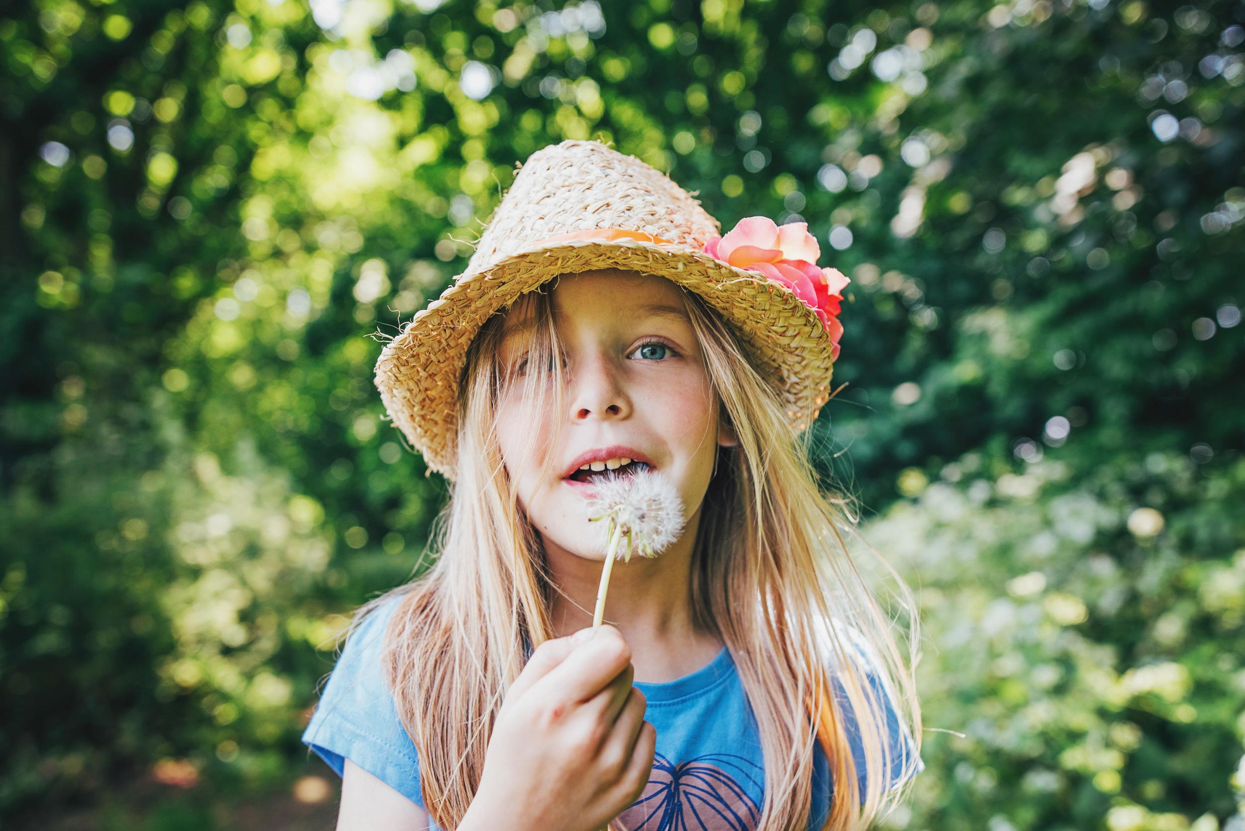Little girl blows dandelion clock Essex UK Documentary Portrait and Lifestyle Photographer