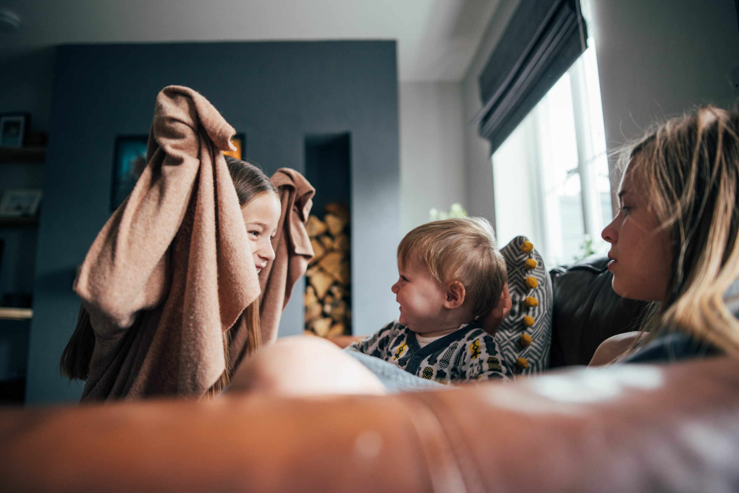 Young girl makes baby boy laugh on sofa Essex UK Documentary Portrait and Lifestyle Photographer
