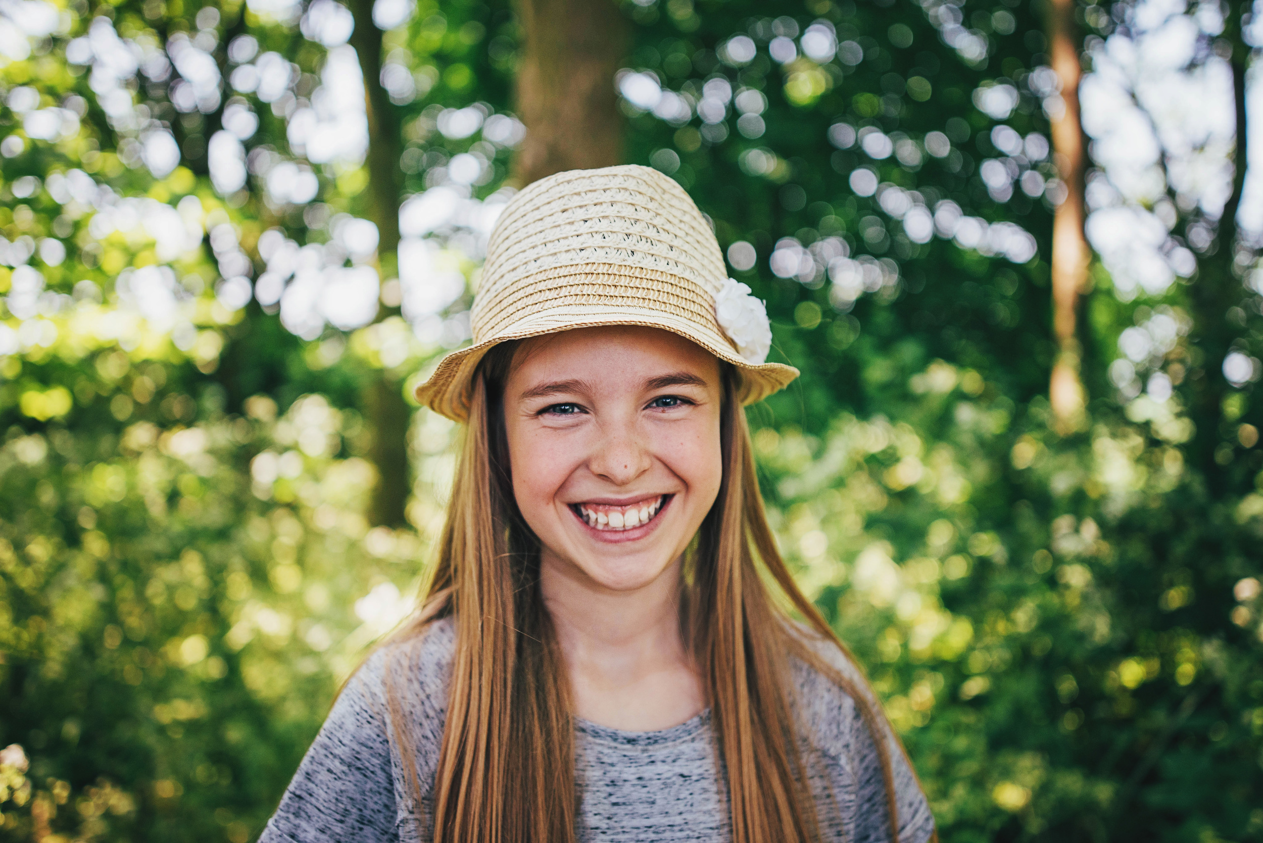 Tween girl in sunhat smiles Essex UK Documentary Portrait and Lifestyle Photographer