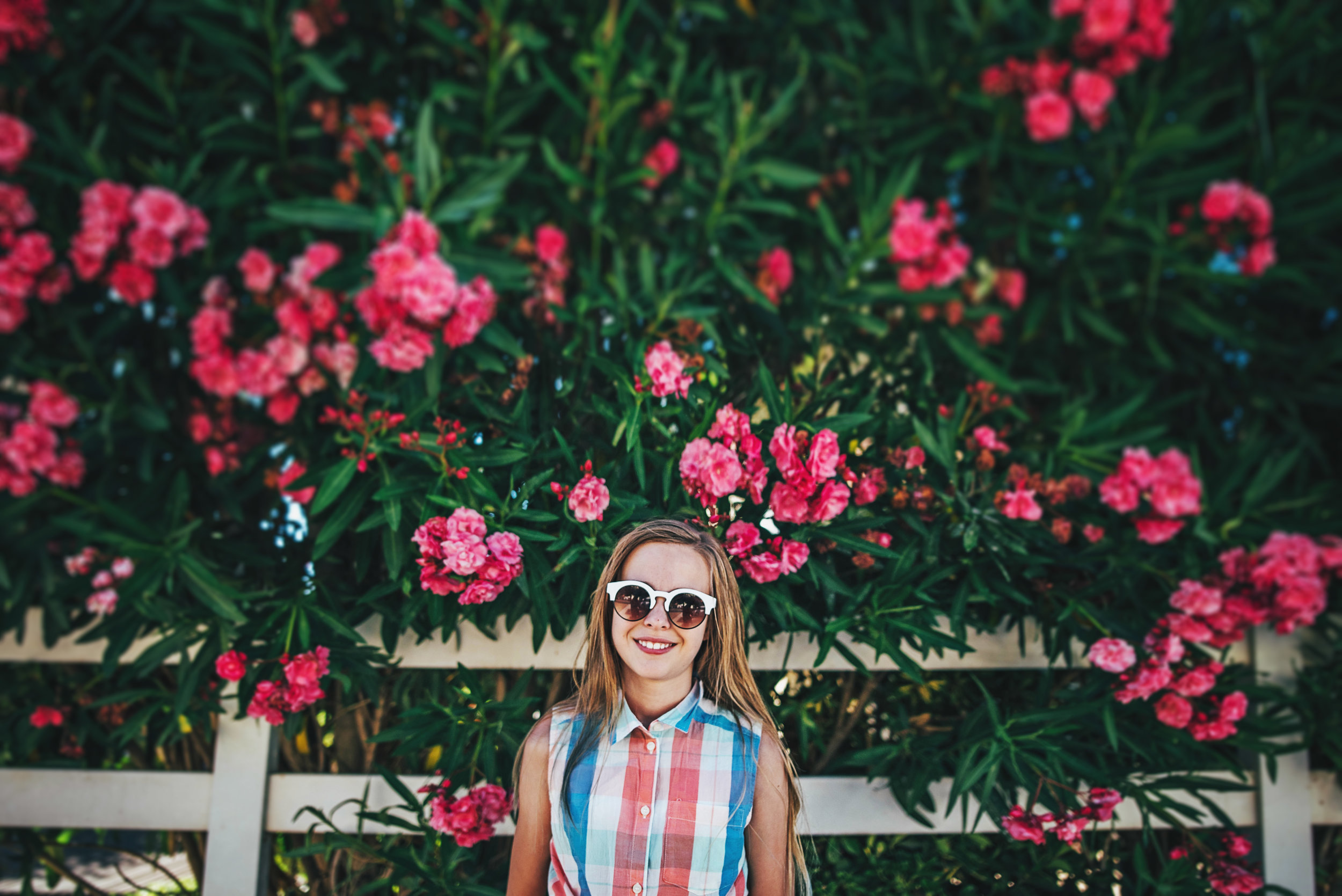 Young girl in sunglasses by pink blossom tree Essex UK Documentary Portrait Photographer