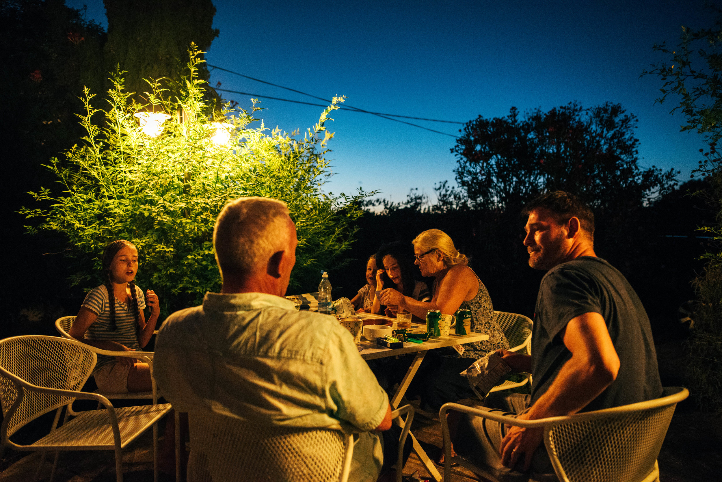 family play cards in garden at night Essex UK Documentary Portrait Photographer