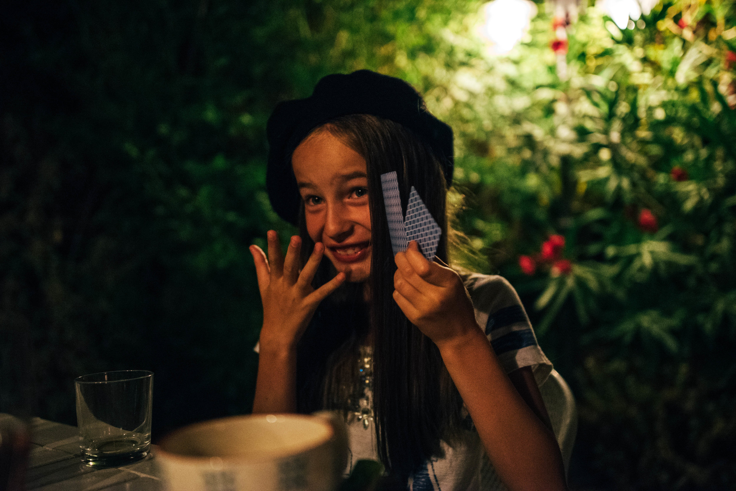 Young girl in beret plays cards in garden at night Essex UK Documentary Portrait Photographer