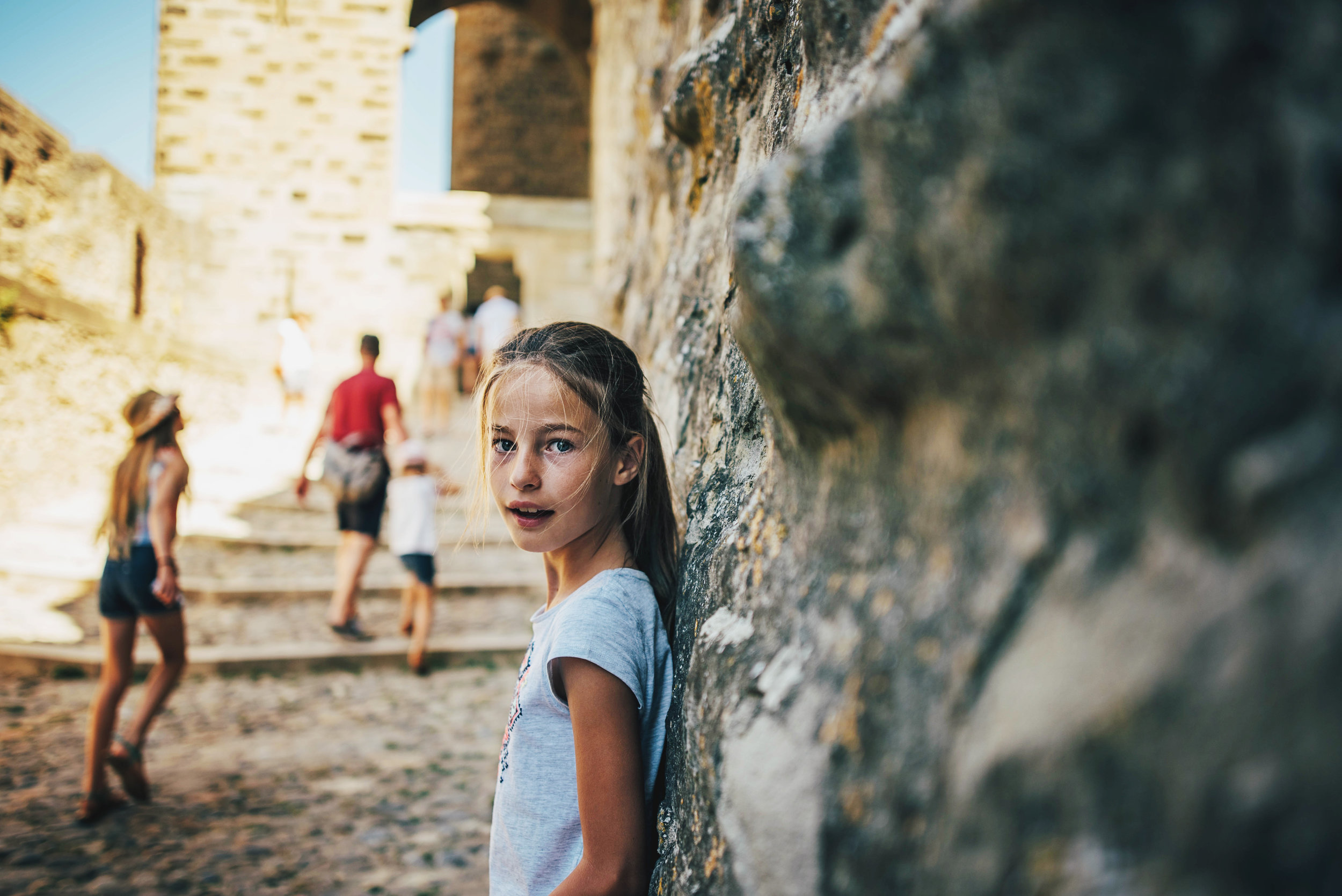 Young girl stands against wall at Carcassonne Citadel France Essex UK Documentary Photographer