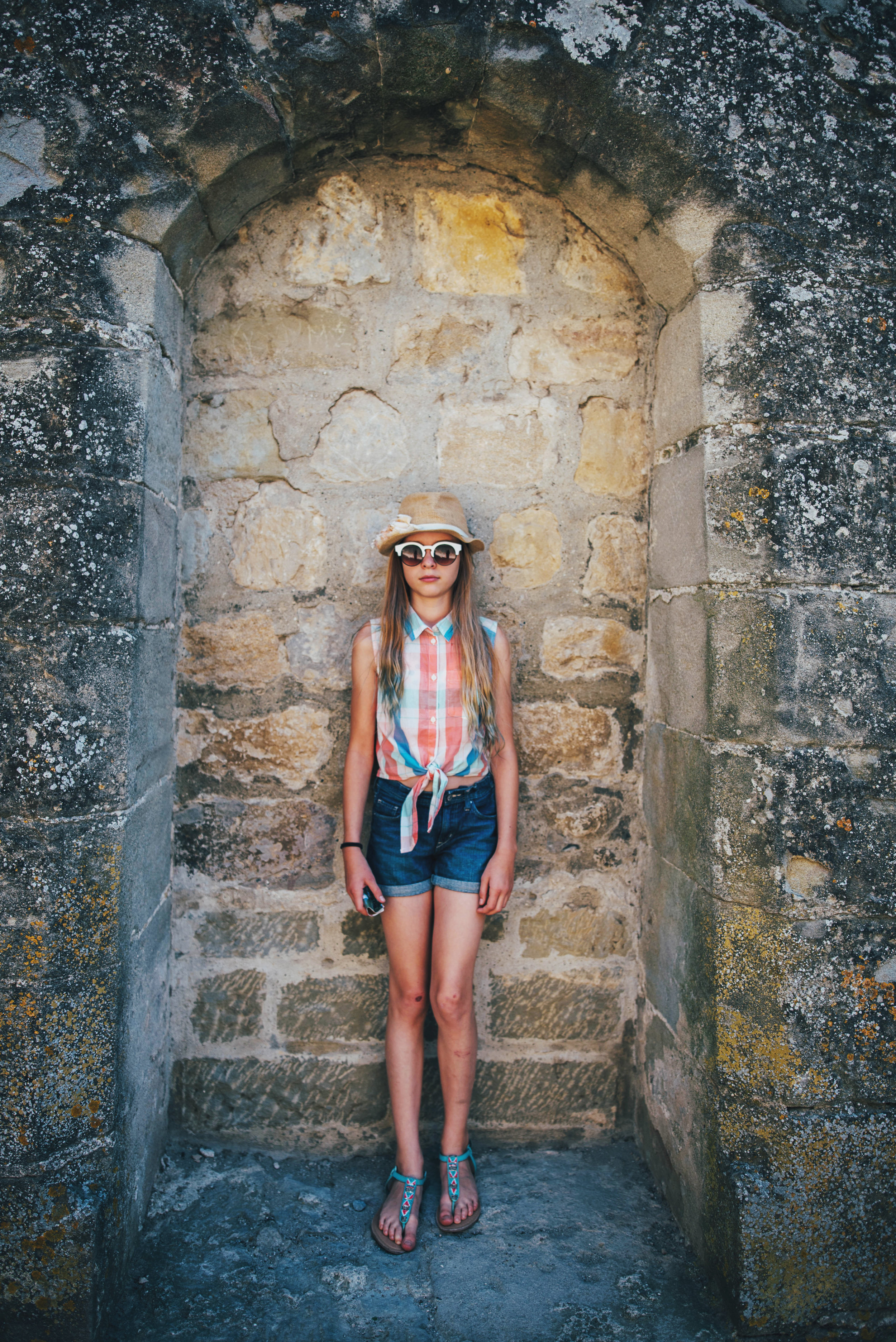 Young girl stands in niche at Carcassonne Citadel Essex UK Documentary Portrait Photographer