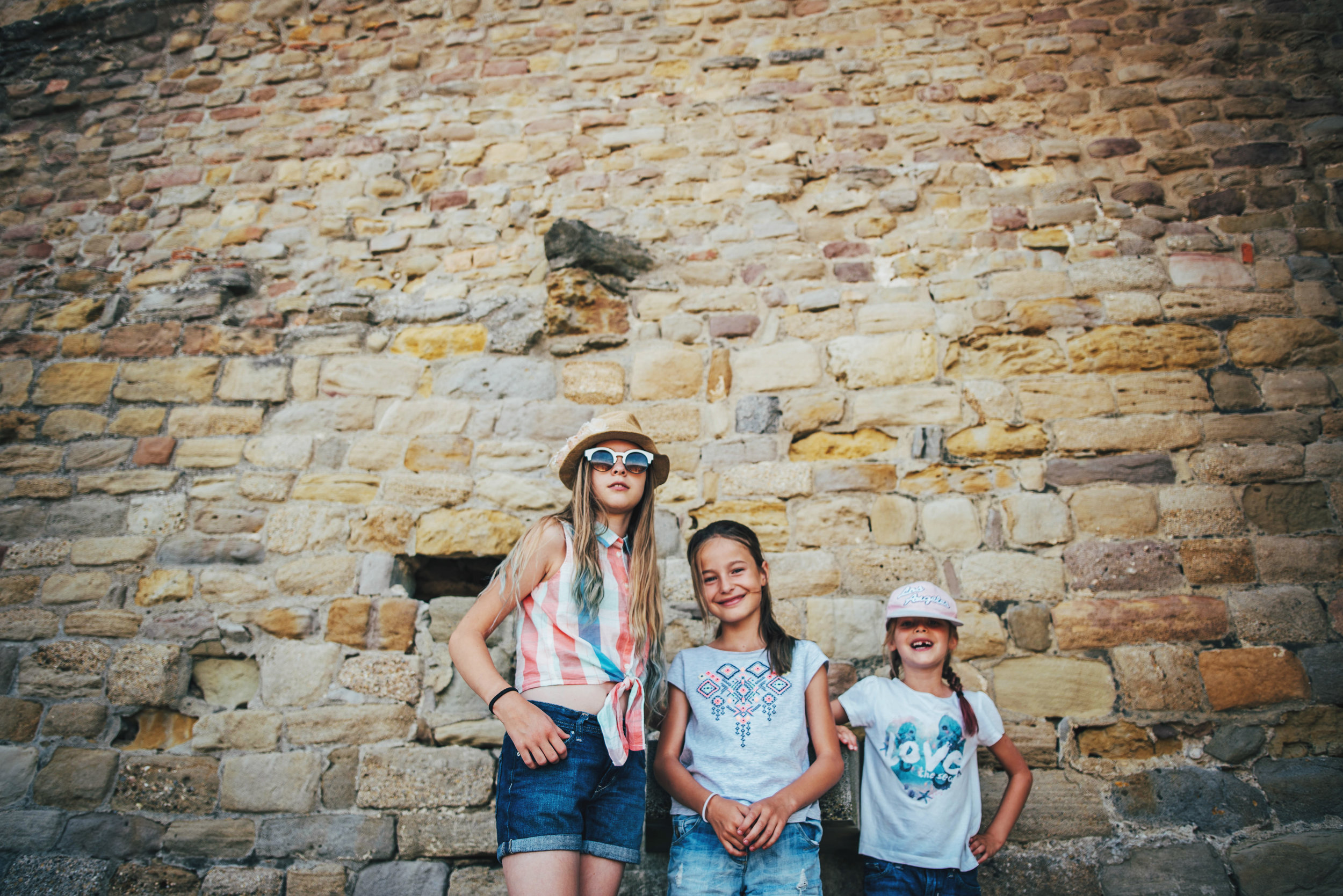 Three girls stand against wall in Carcassonne Citadel France Essex UK Documentary Portrait Photographer