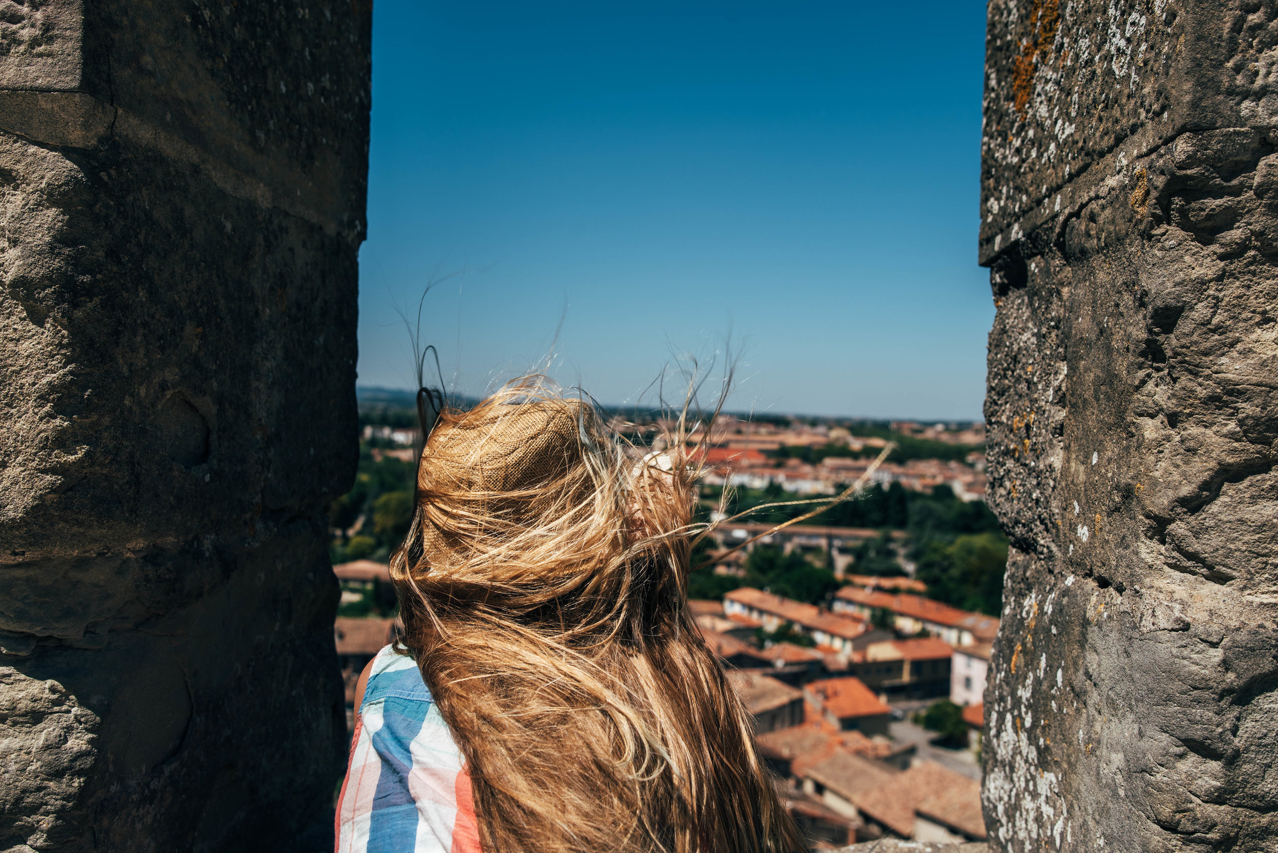Young girl looks out over Carcassonne from the Citadel France Essex UK Documentary Photographer