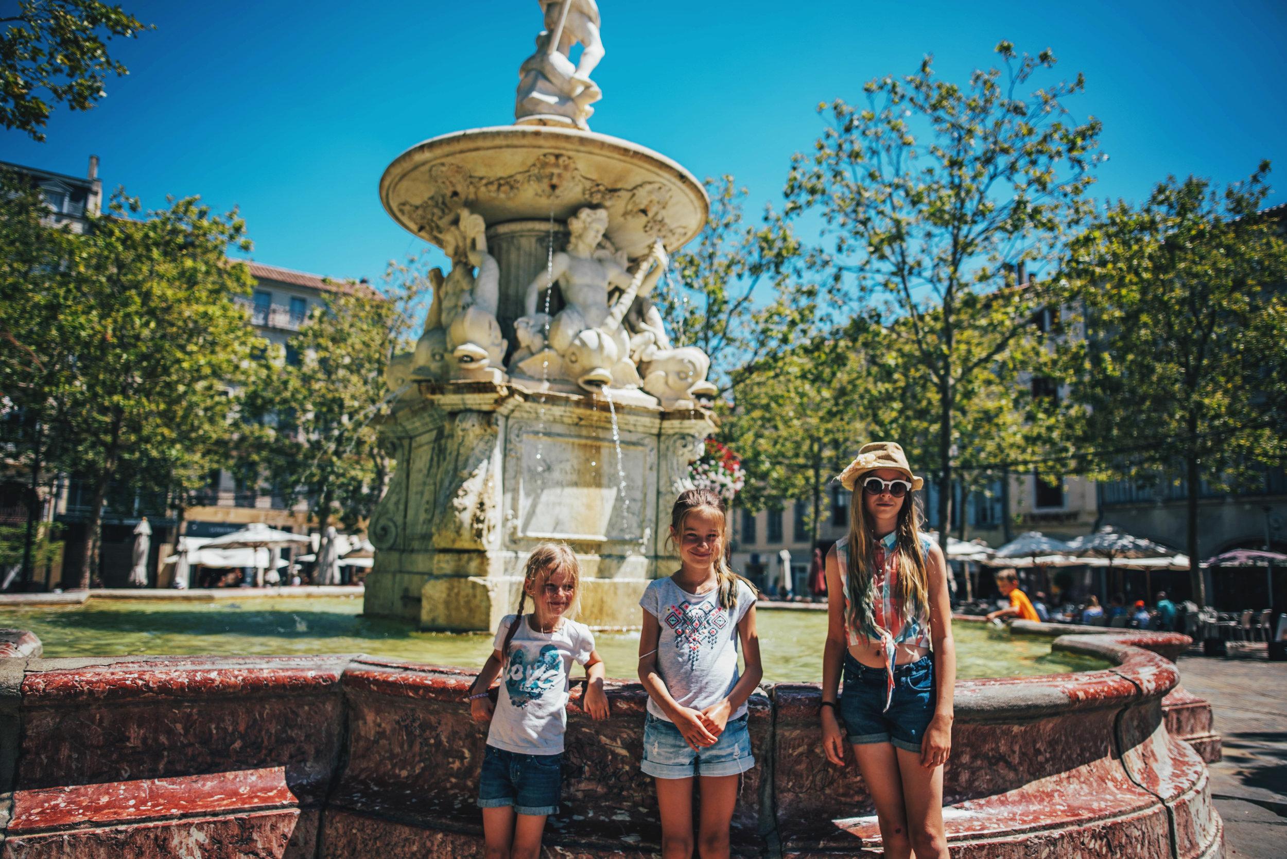 Three girls by La Fontaine de Neptune Carcassonne France Essex UK Documentary Photographer