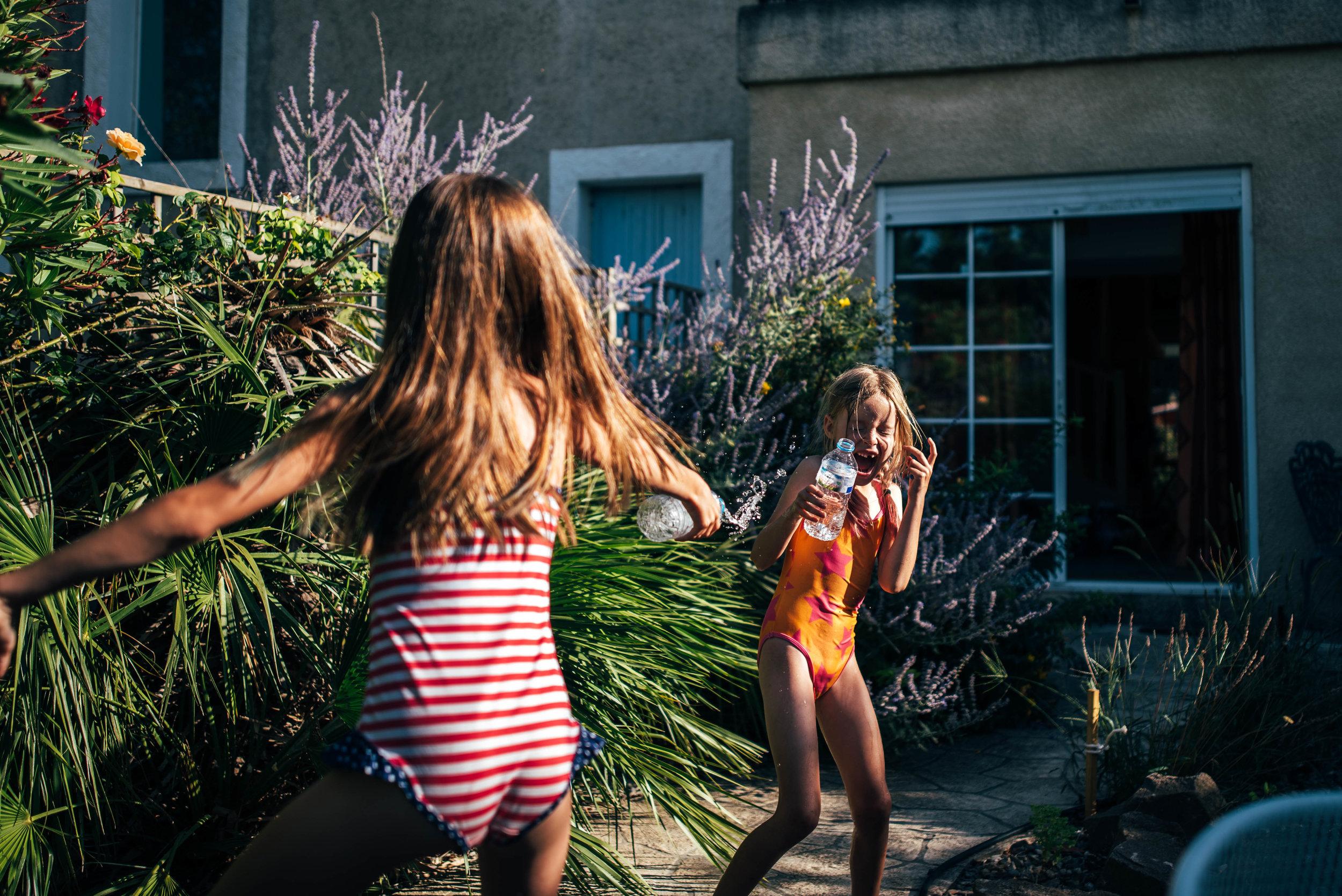 Girls have water fight in garden Essex UK Documentary Photographer