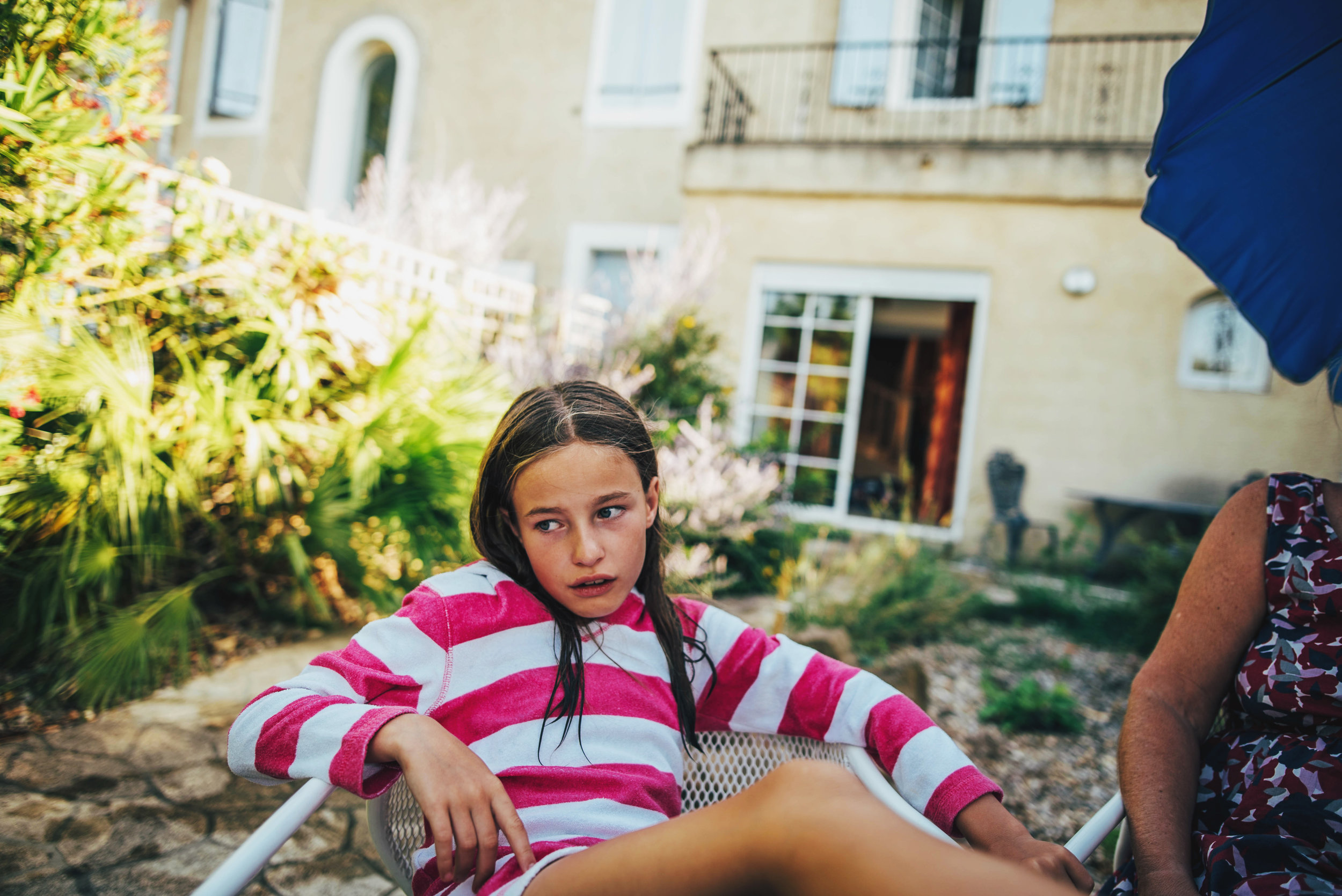 Young girl sits in holiday garden Essex UK Documentary Portrait Photographer
