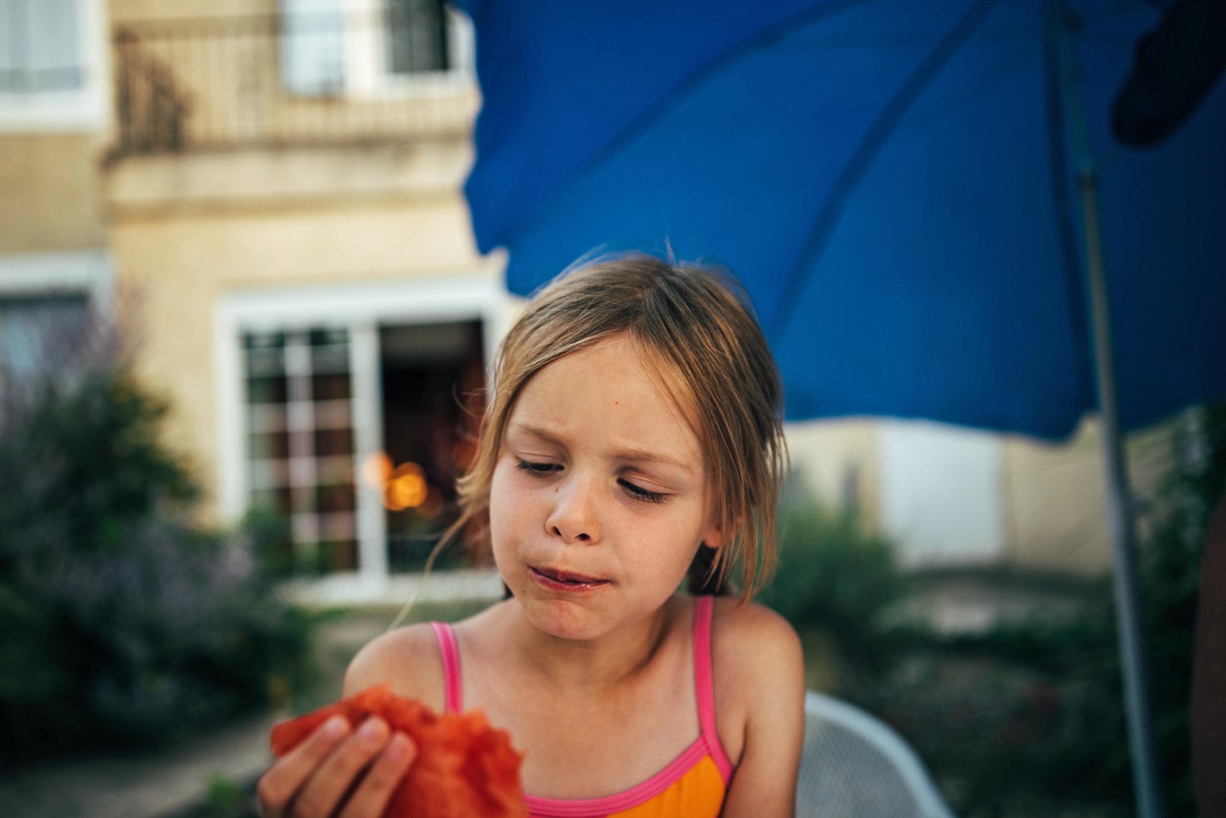 Little girl eats melon on holiday Essex UK Documentary Portrait Photographer