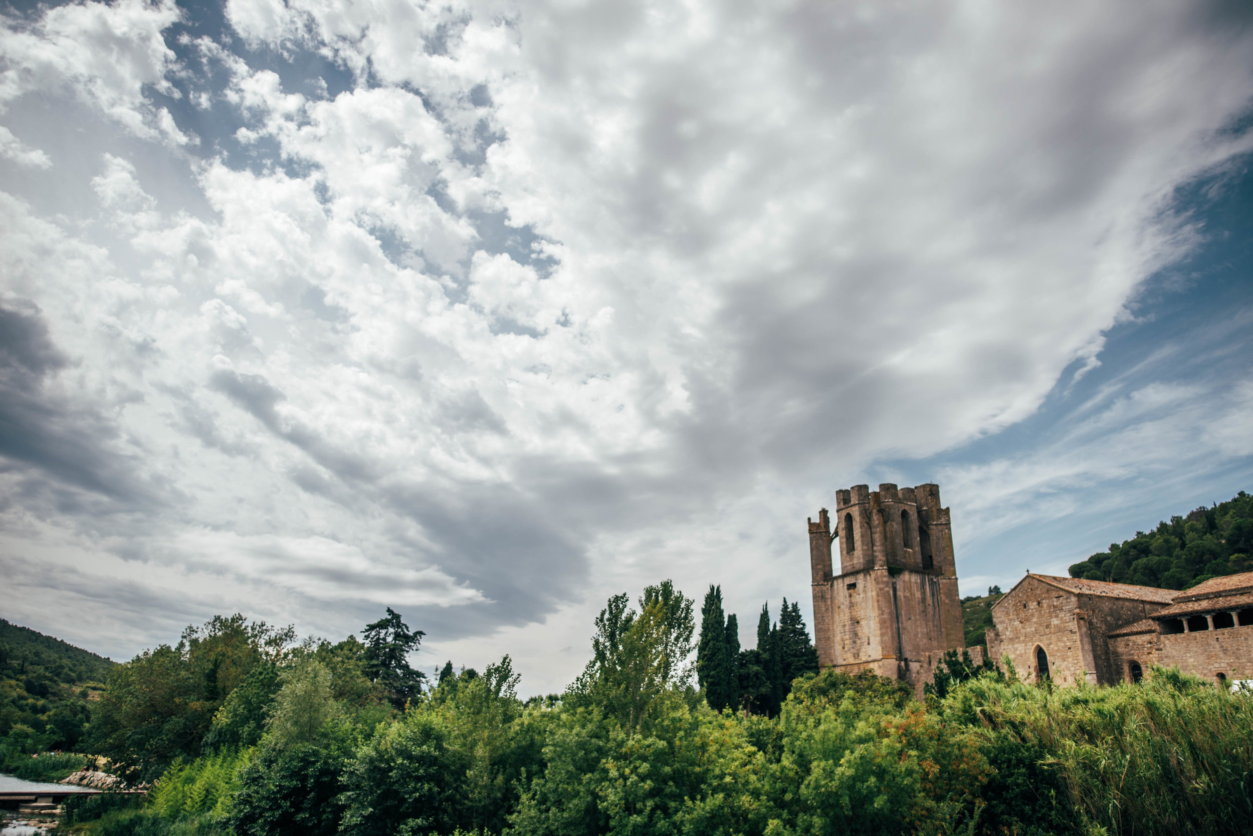 Church on river bank in Lagrasse France Essex UK Documentary Photographer