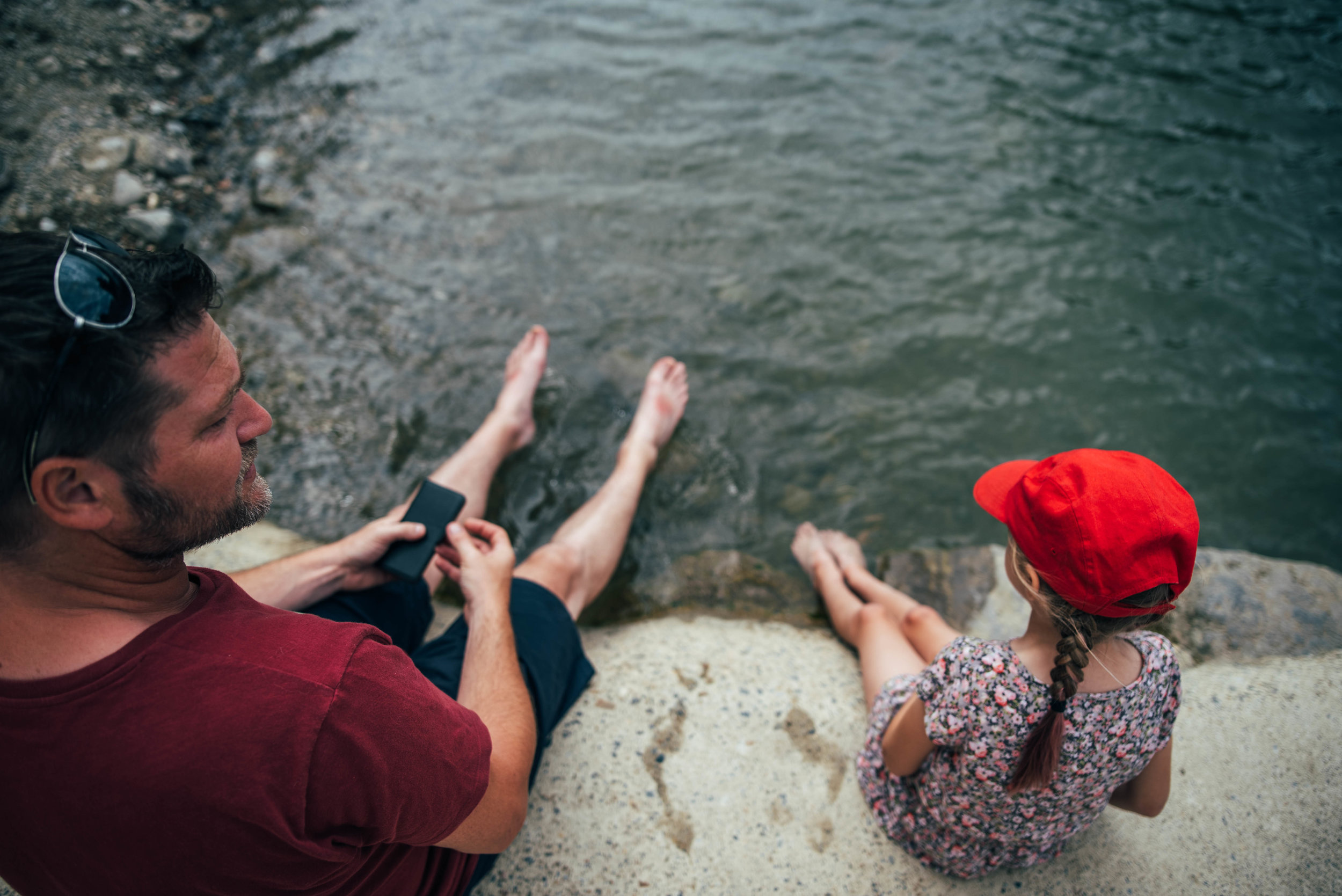 Dad and daughter paddle in river in Lagrasse France Essex UK Documentary Photographer