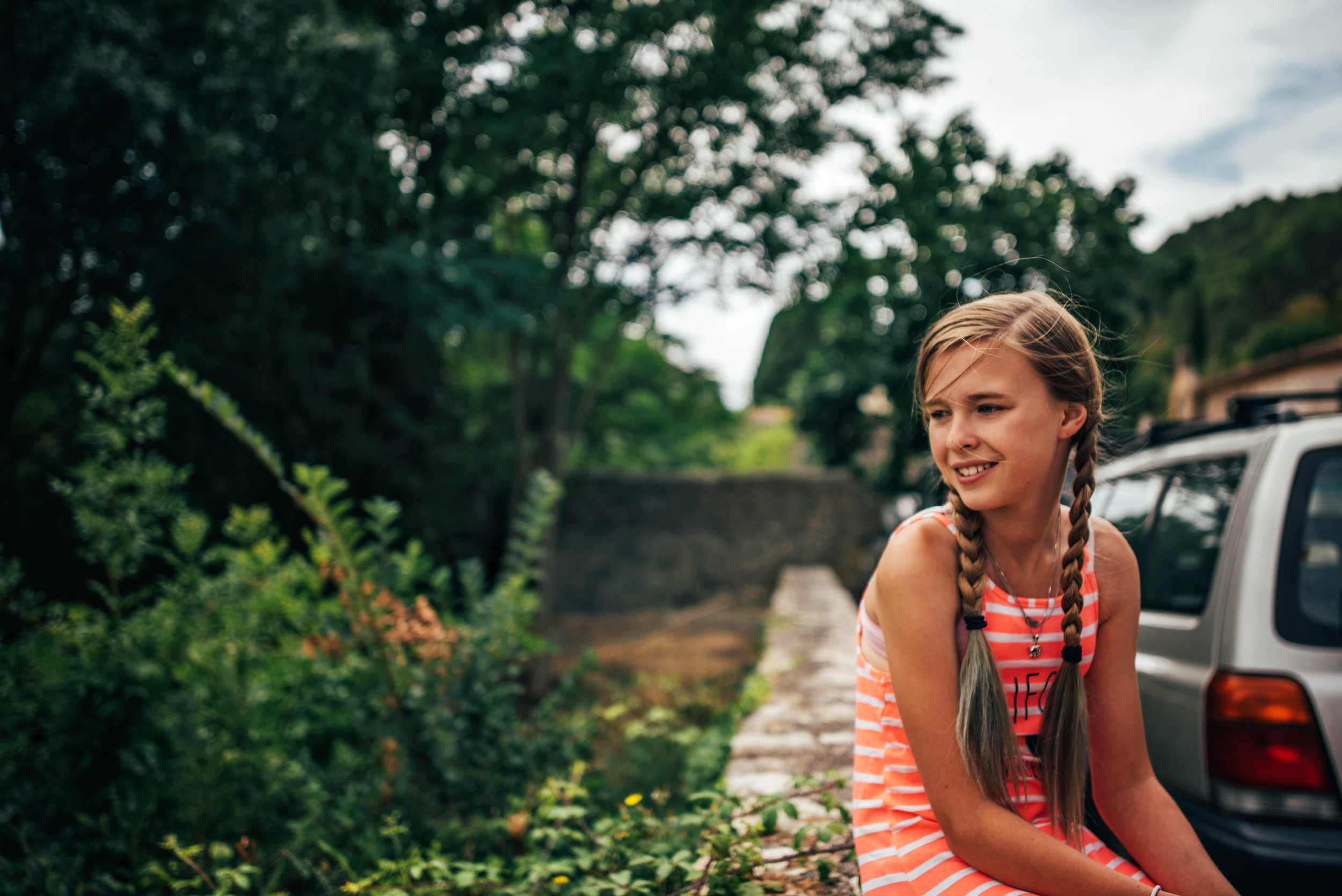 Girl sits on wall in Lagrasse France Essex UK Documentary Portrait Photographer