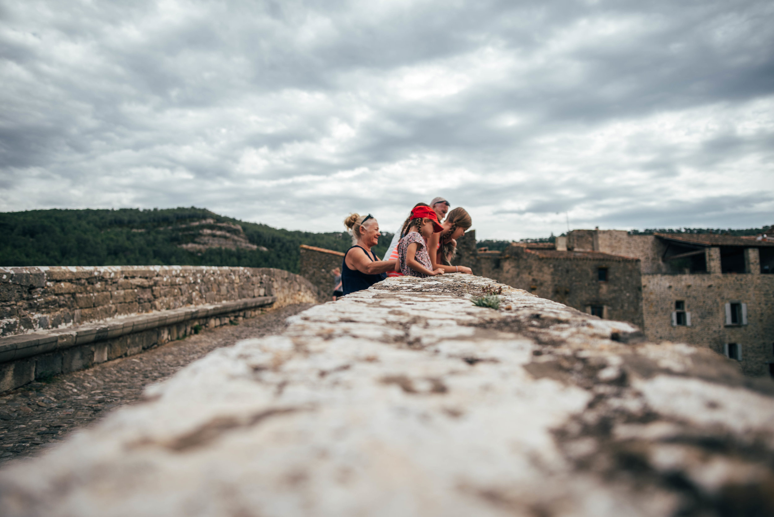 Family stand on bridge over river at Lagrasse France Essex UK Documentary Portrait Photographer