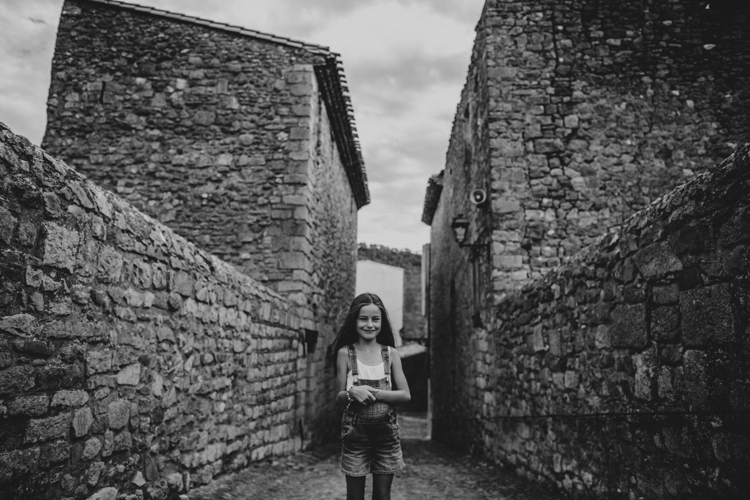 Young girl stand on bridge at Lagrasse France Essex UK Documentary Portrait Photographer
