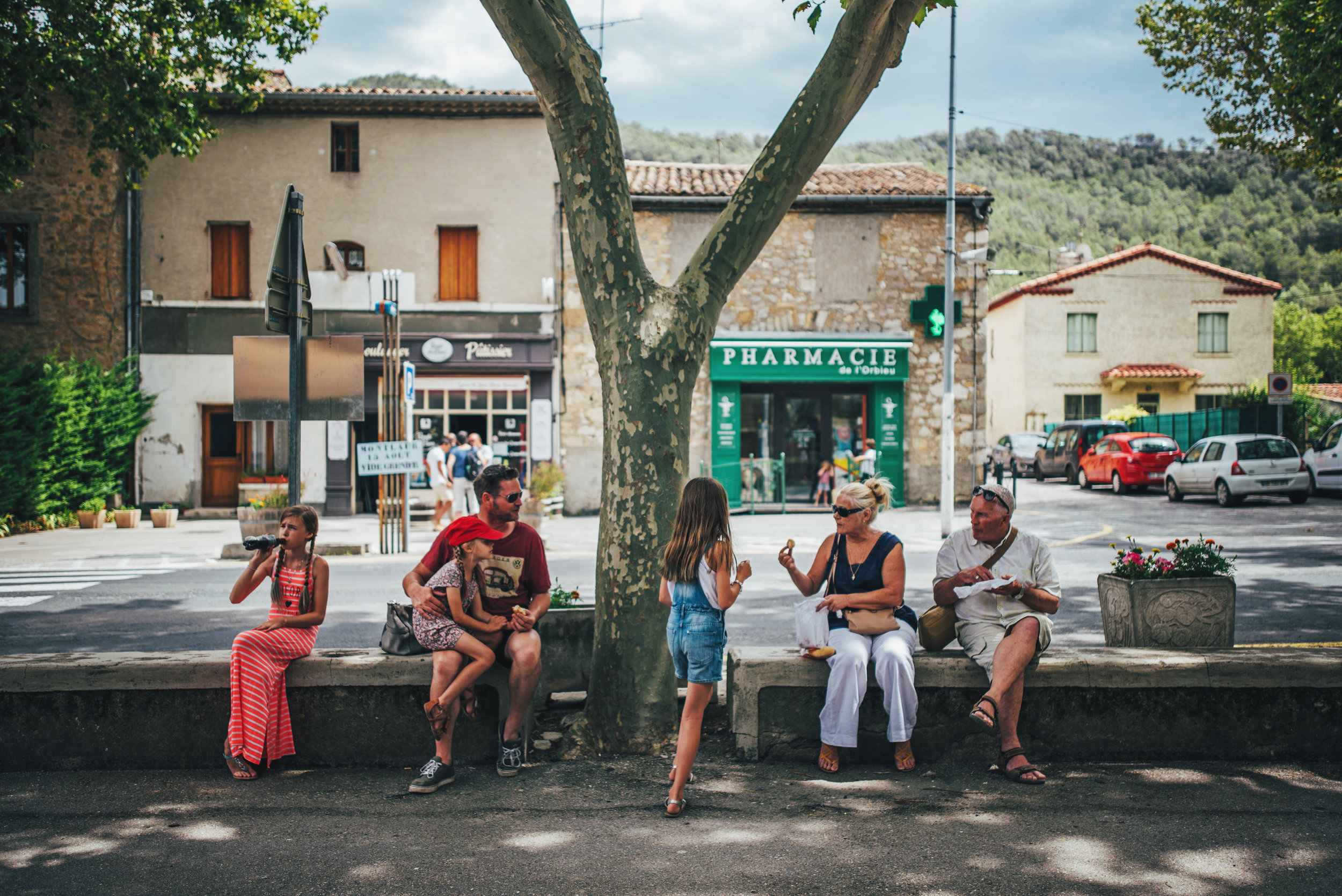 Family eat lunch on wall in Lagrasse France Essex UK Documentary Portrait Photographer