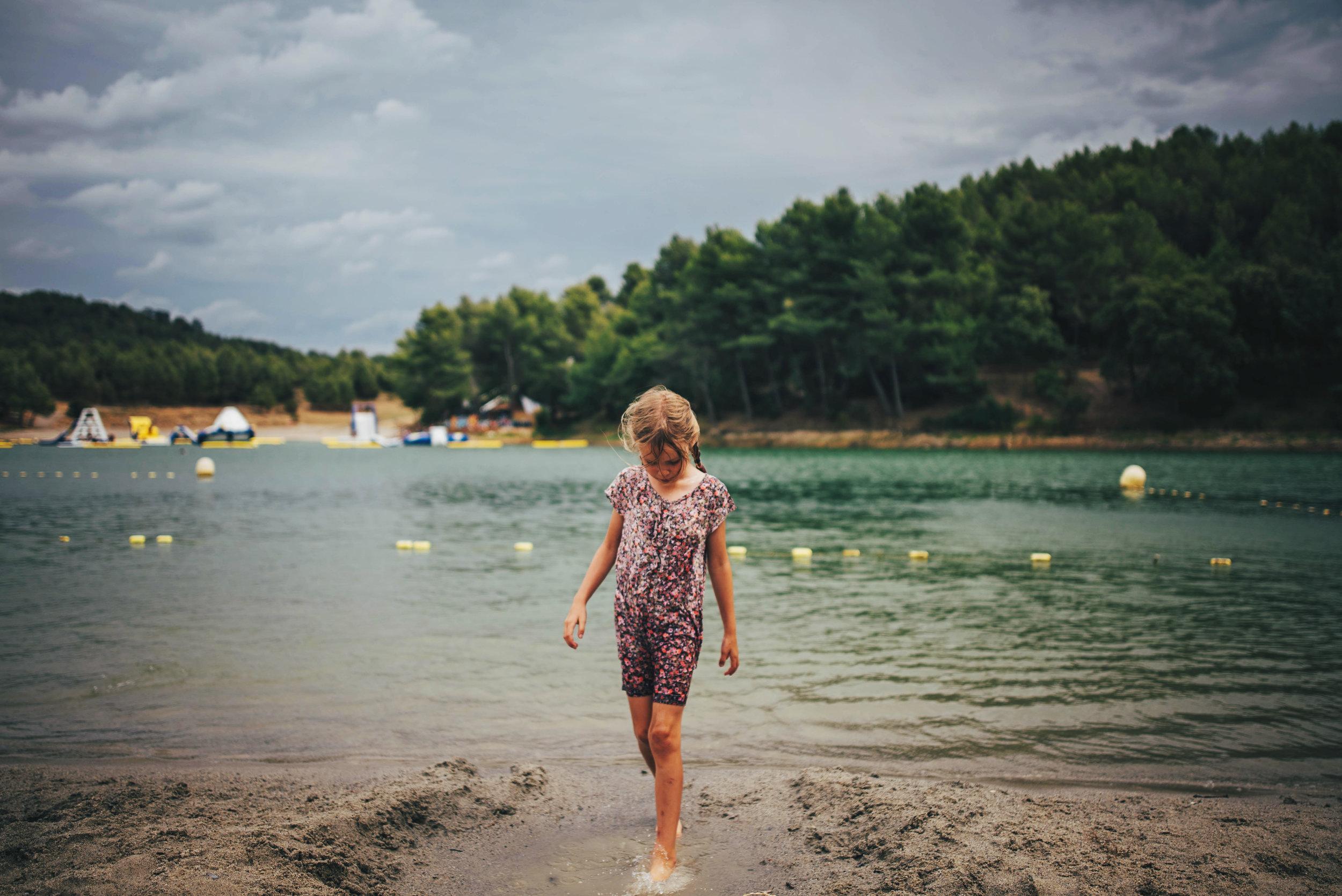 Young girl walks into Lake Essex UK Documentary Portrait Photographer