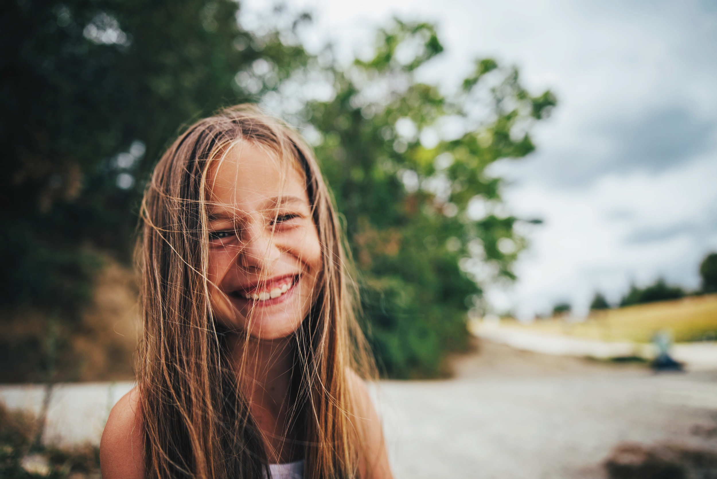 Young girl on beach laughs at camera Essex UK Documentary Portrait Photographer