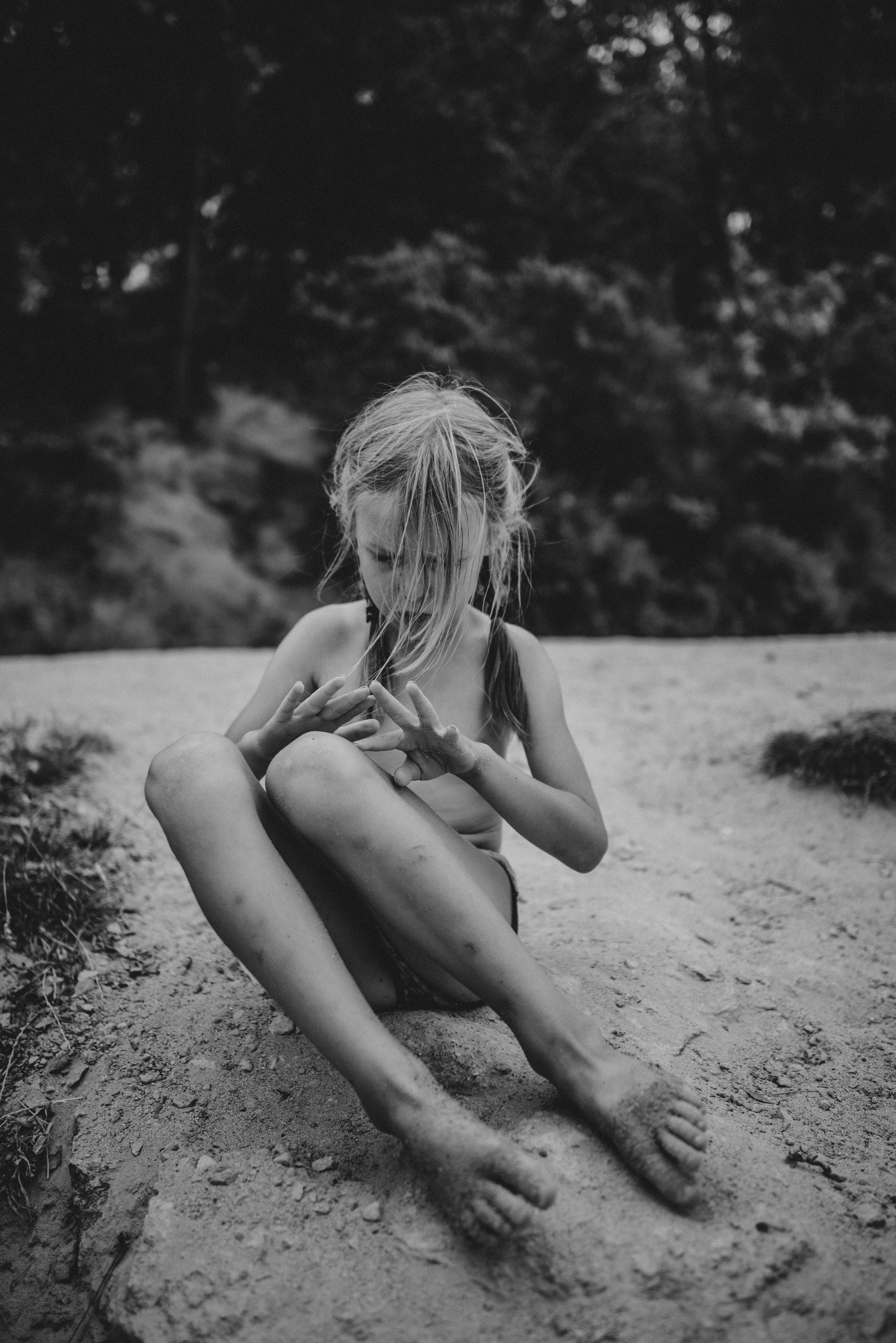 Young girl on beach looks at shell Essex UK Documentary Portrait Photographer