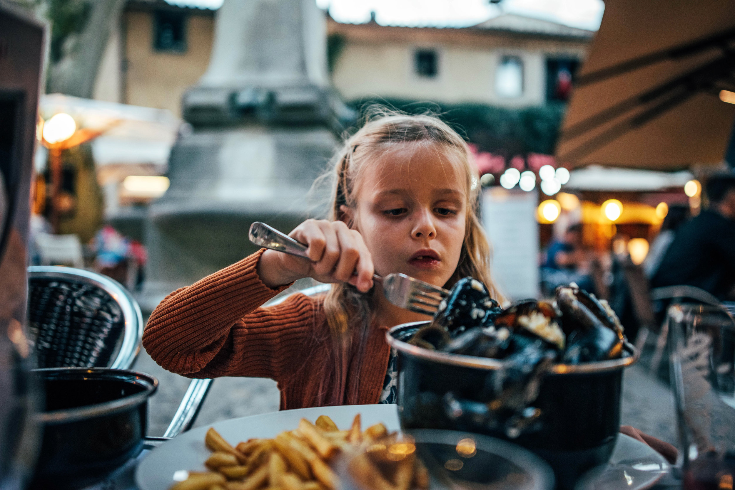 Young girl eats mussels Essex UK Documentary Photographer