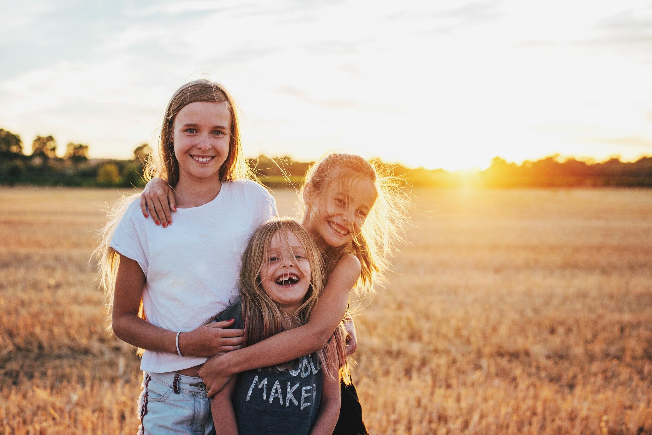 Three girls at sunset in cornfield Essex UK Documentary Portrait Photographer