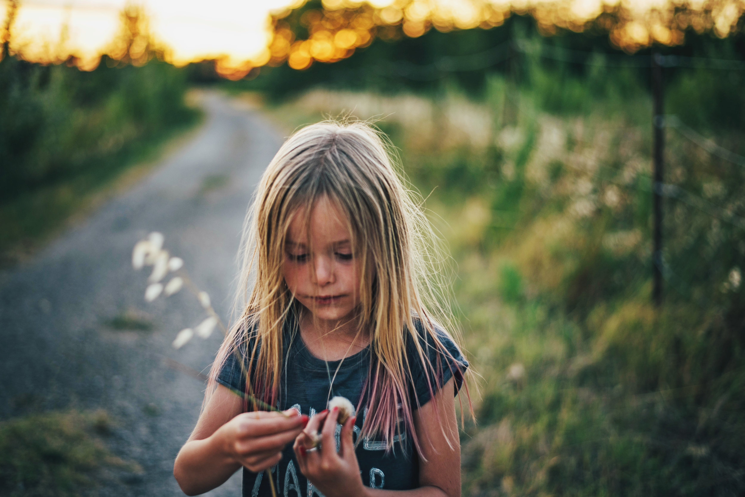 Young girl looks at flower Essex UK Documentary Portrait Photographer