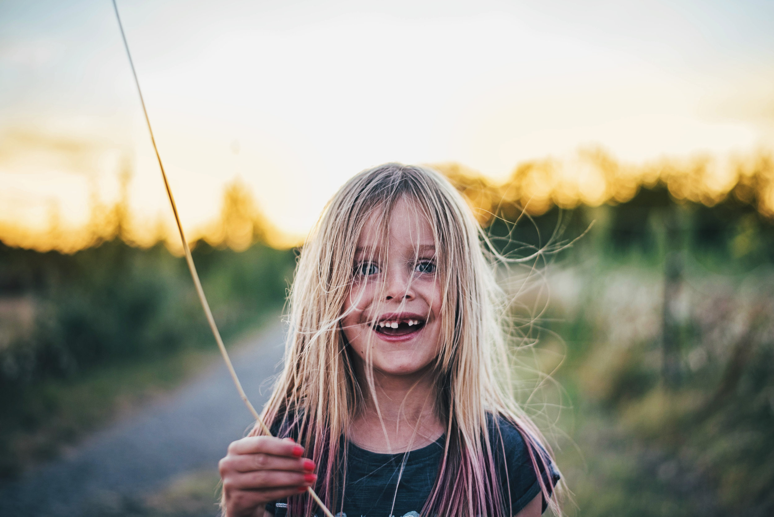 Young girl holds up blade of grass Essex uK Documentary Portrait Photographer