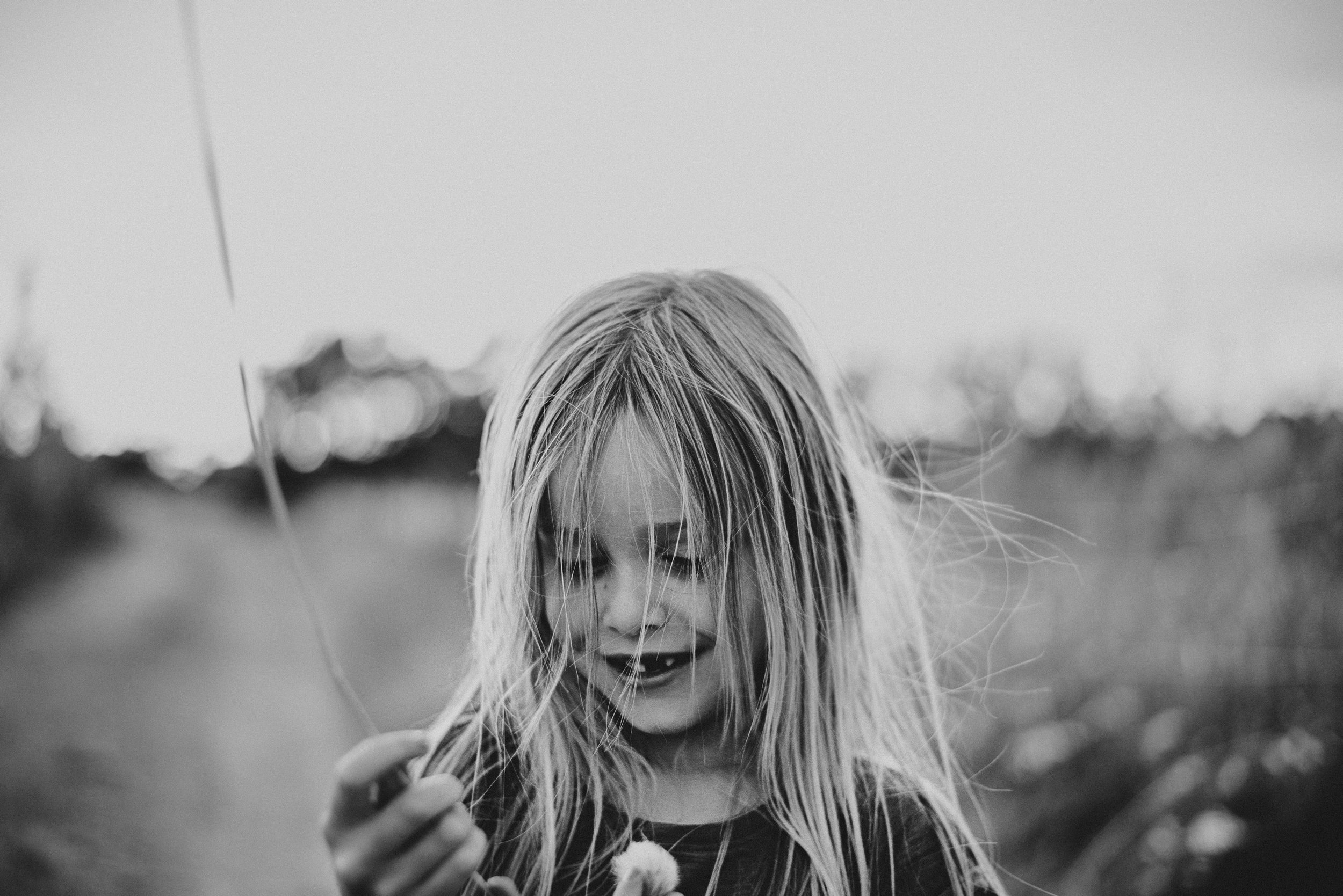 Young girl holds grass Essex UK Documentary Portrait Photographer
