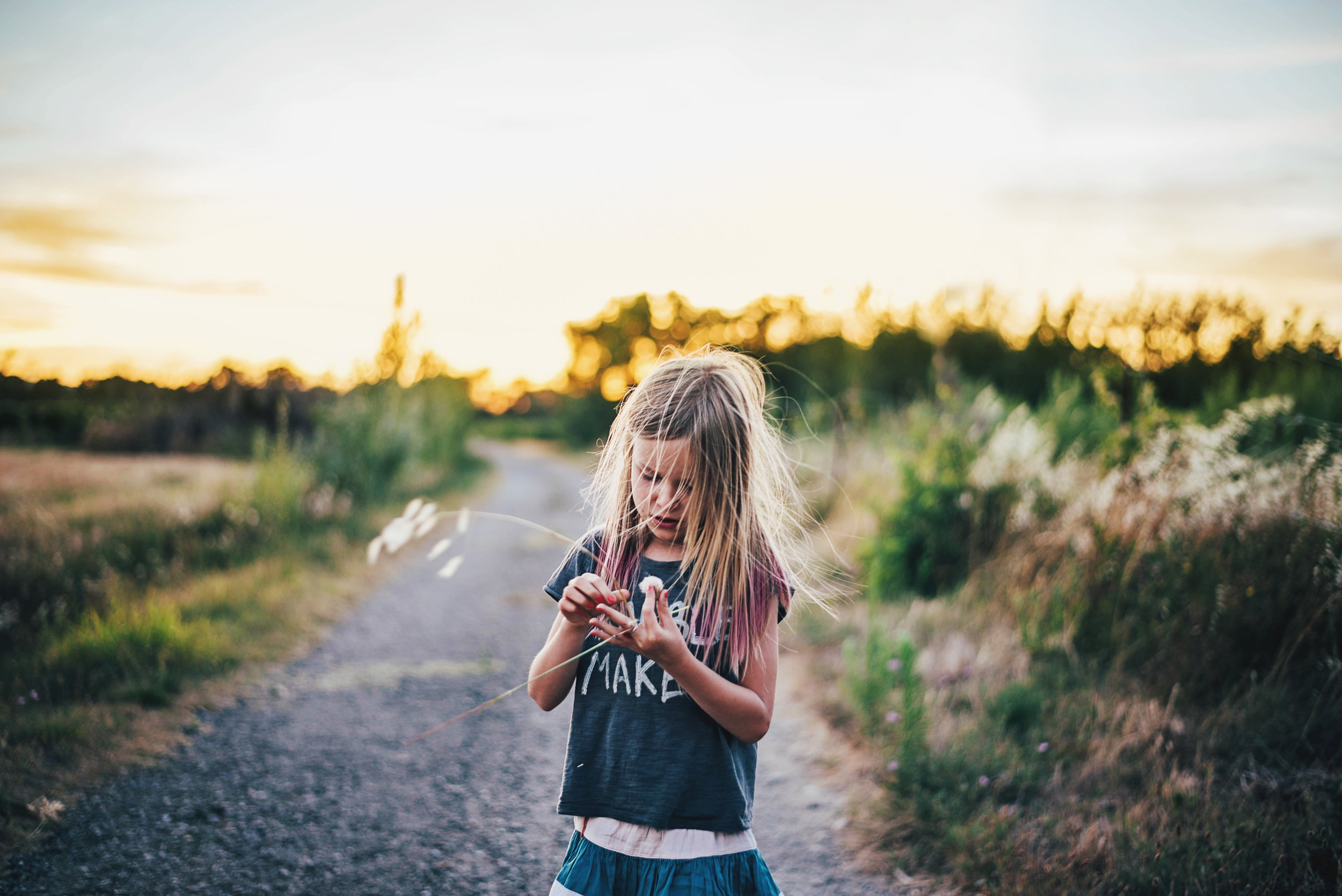 Young girl on country path holds long grass Essex UK Documentary Portrait Photographer