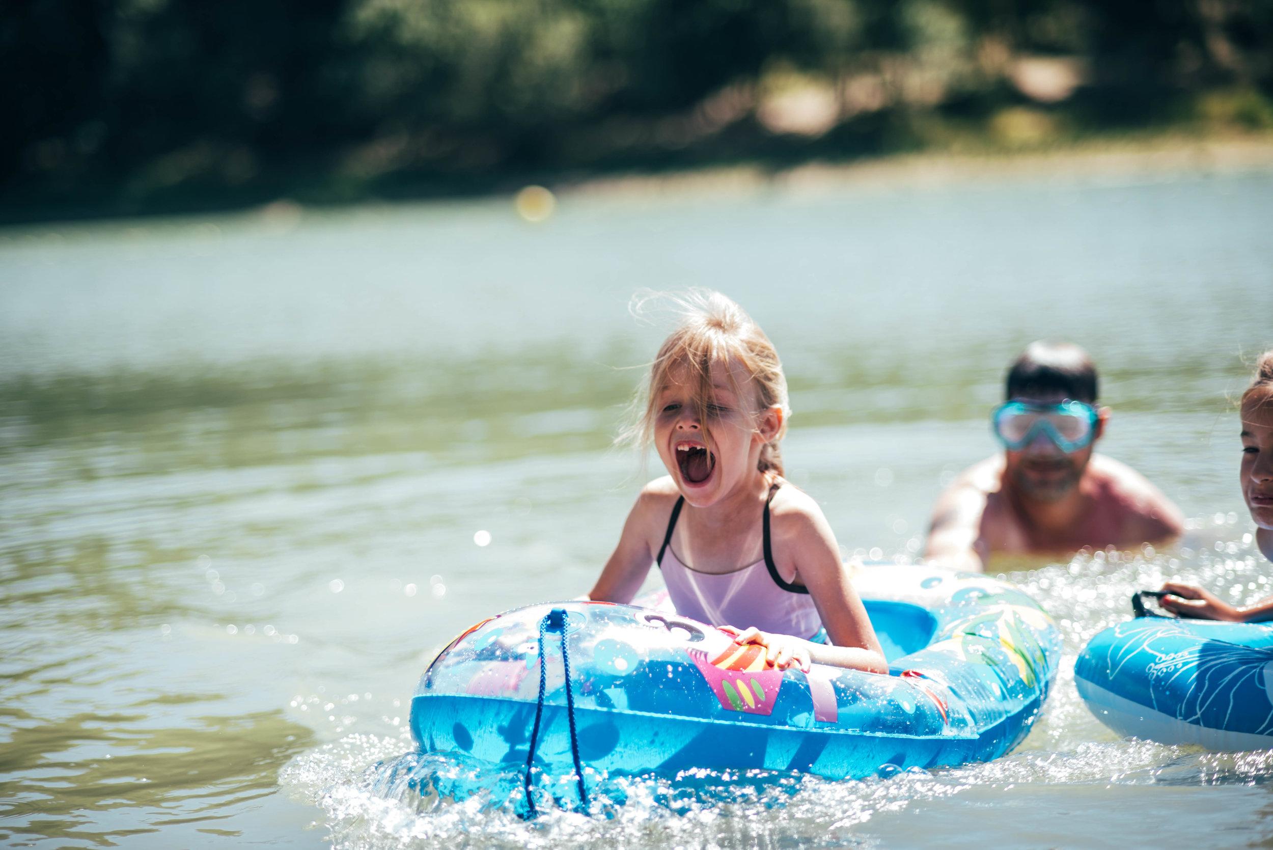 Little girl laughs in boat on lake Essex UK Documentary Portrait Photographer