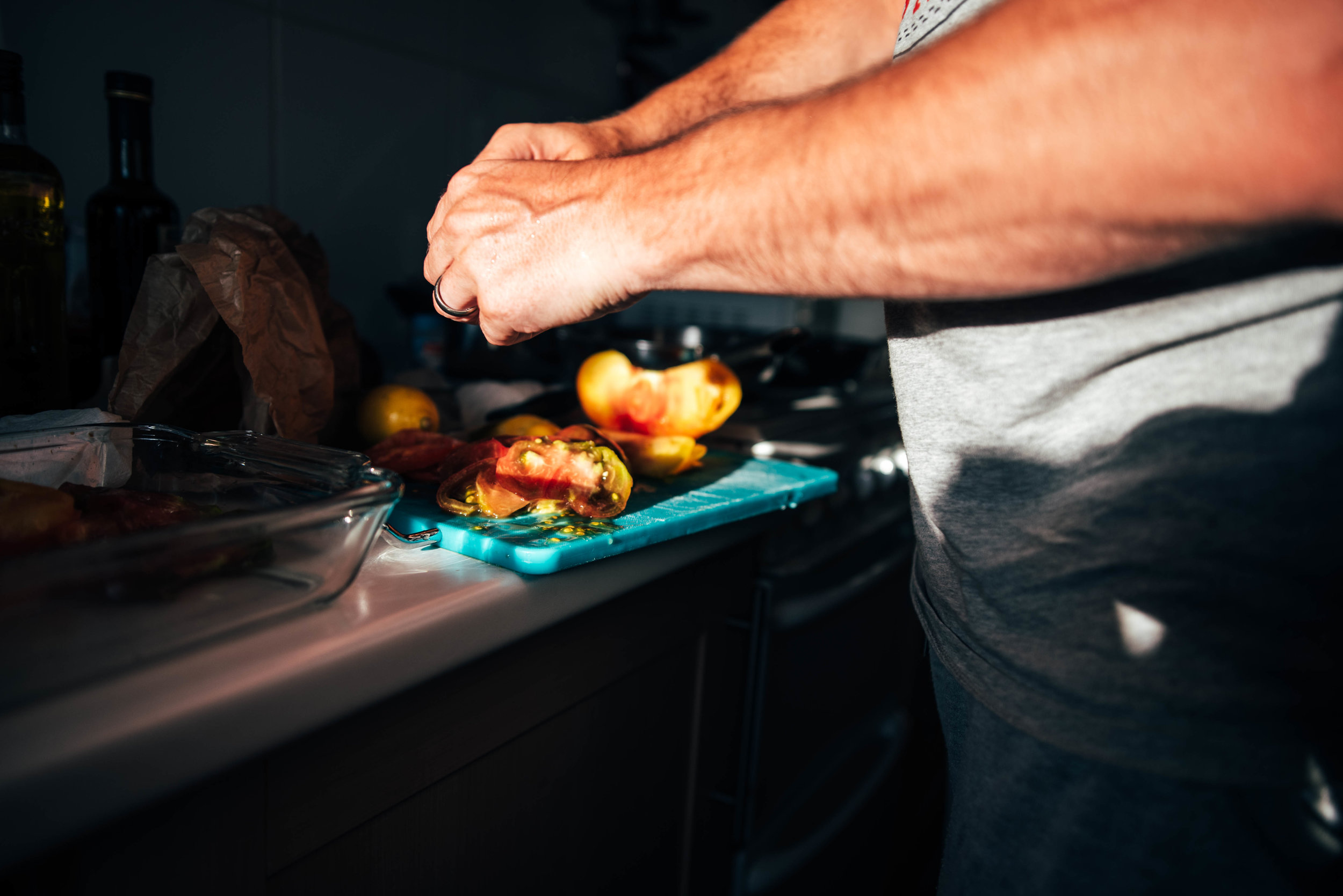Man prepares dinner in sun drenched kitchen Essex UK Documentary Photographer