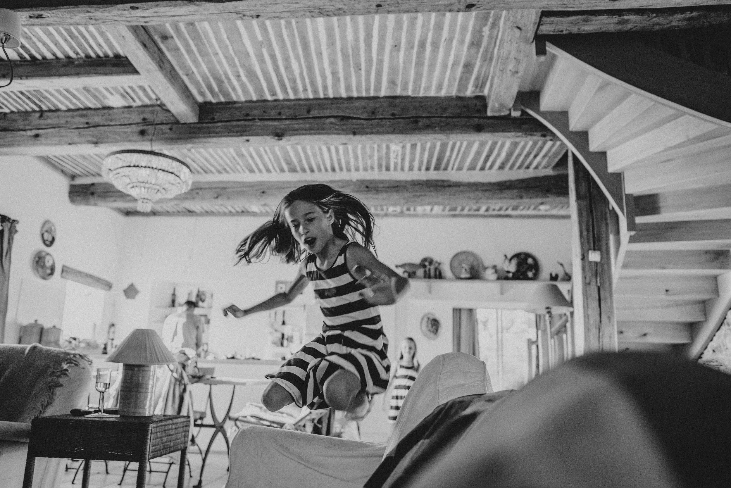 Girl jumps on sofa Essex UK Documentary Photographer