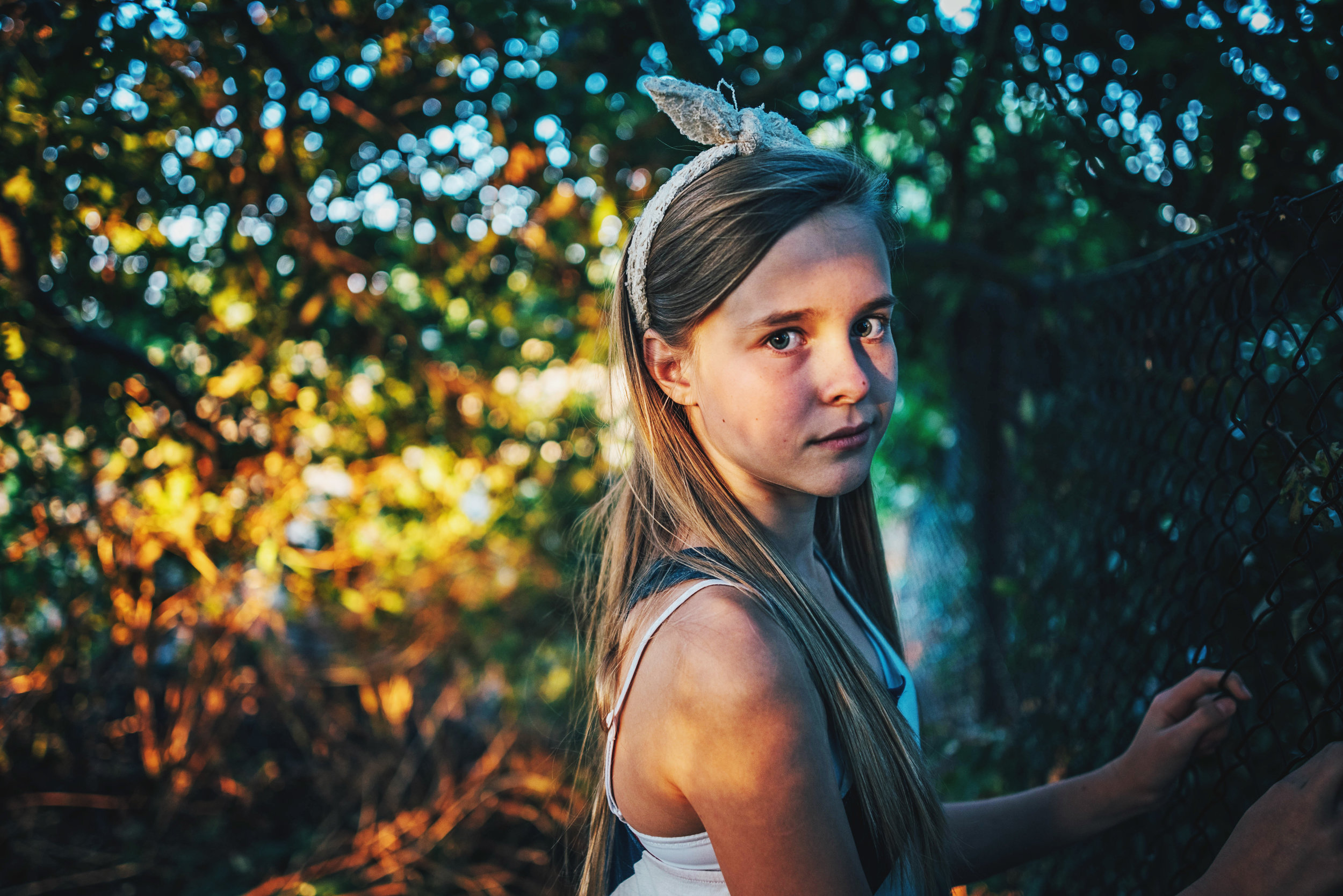 Girl stands among trees at sunset golden hour Essex UK Documentary Portrait Photographer
