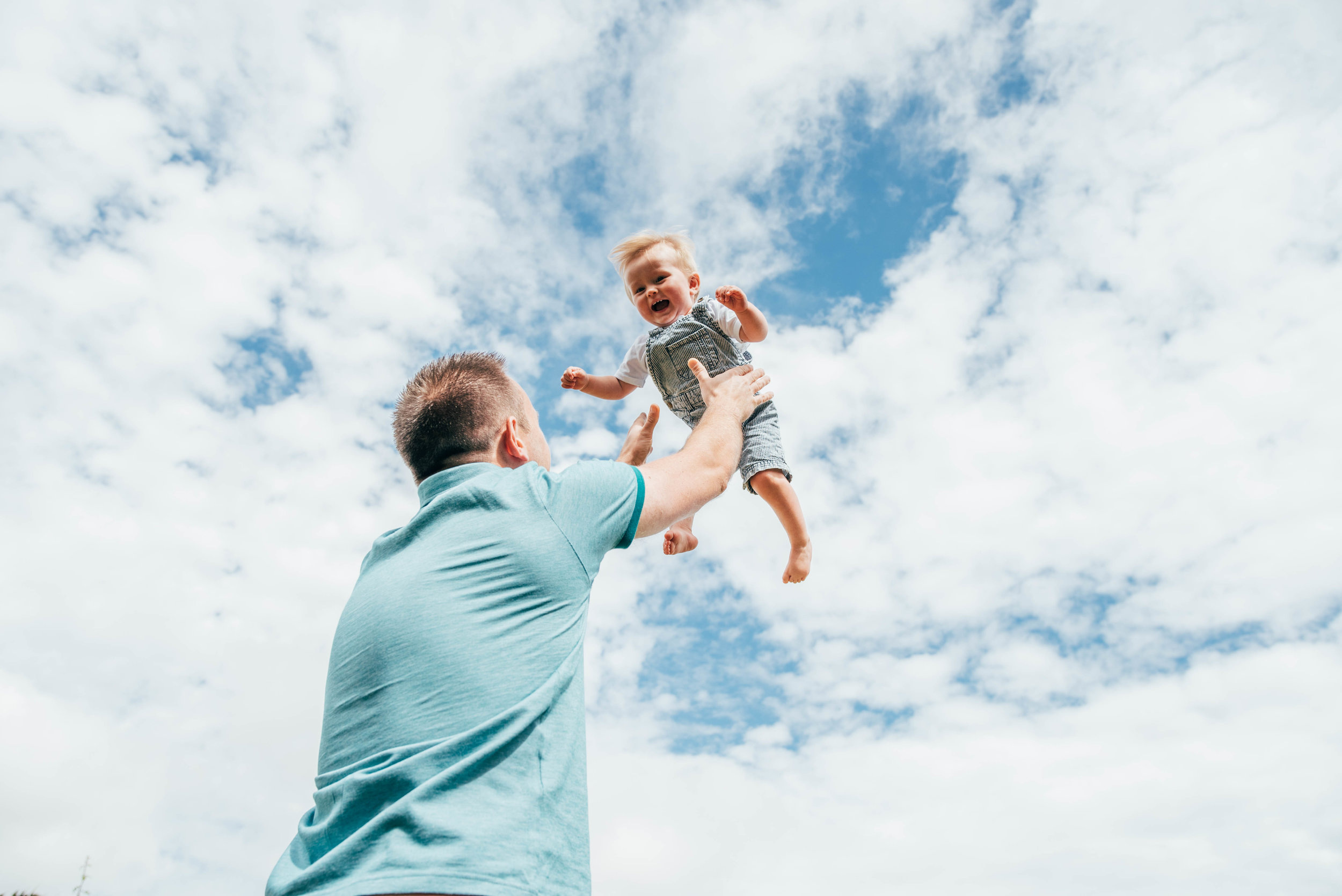 Dad holds baby boy up to the sky Essex UK Documentary Portrait Photographer