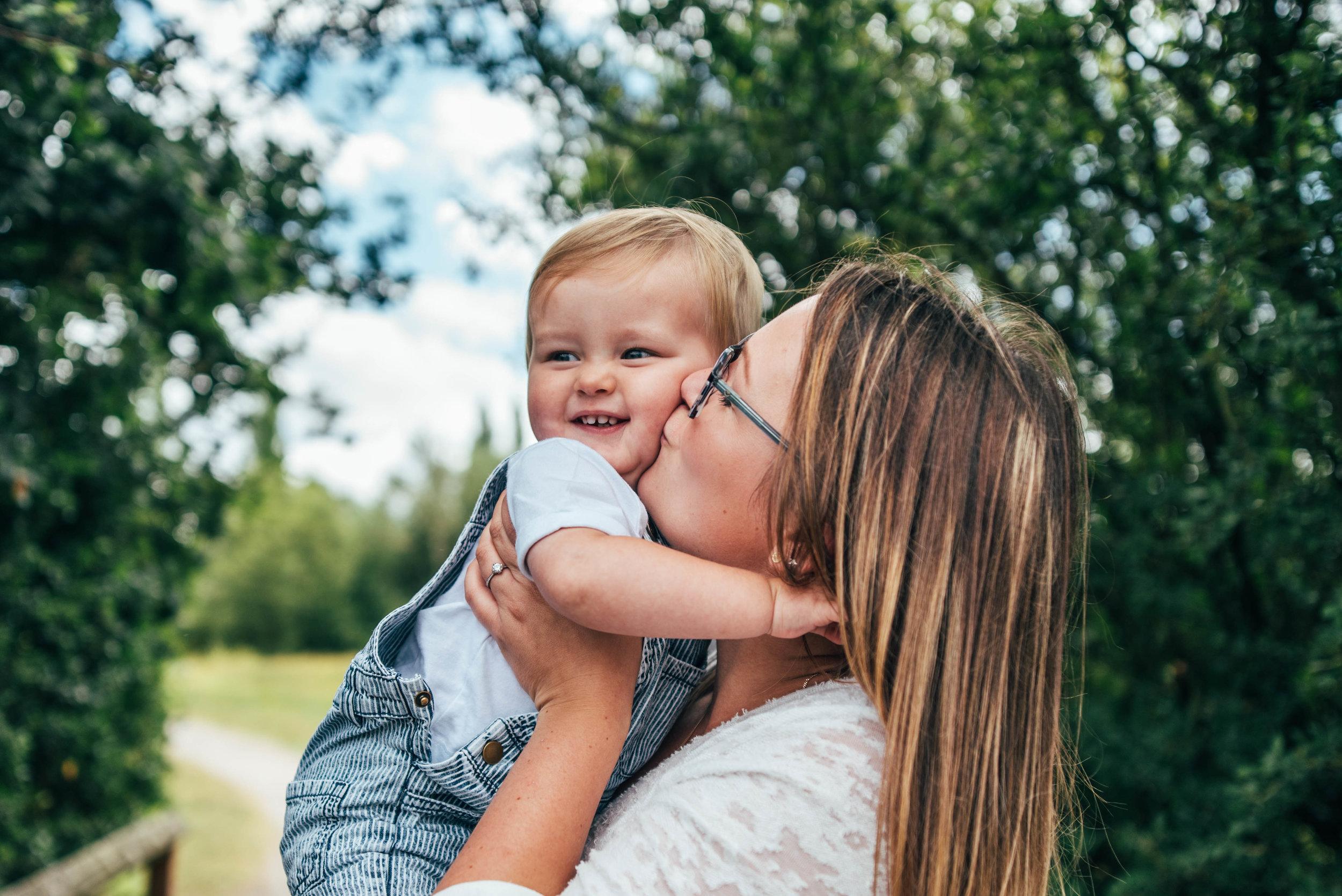 Mum kisses baby boy Essex UK Documentary Portrait Photographer