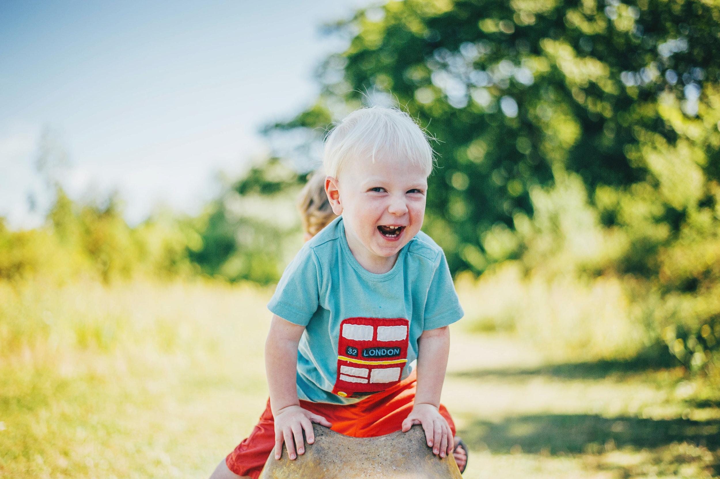 Little boy laughs in park Essex UK Documentary Portrait Photographer