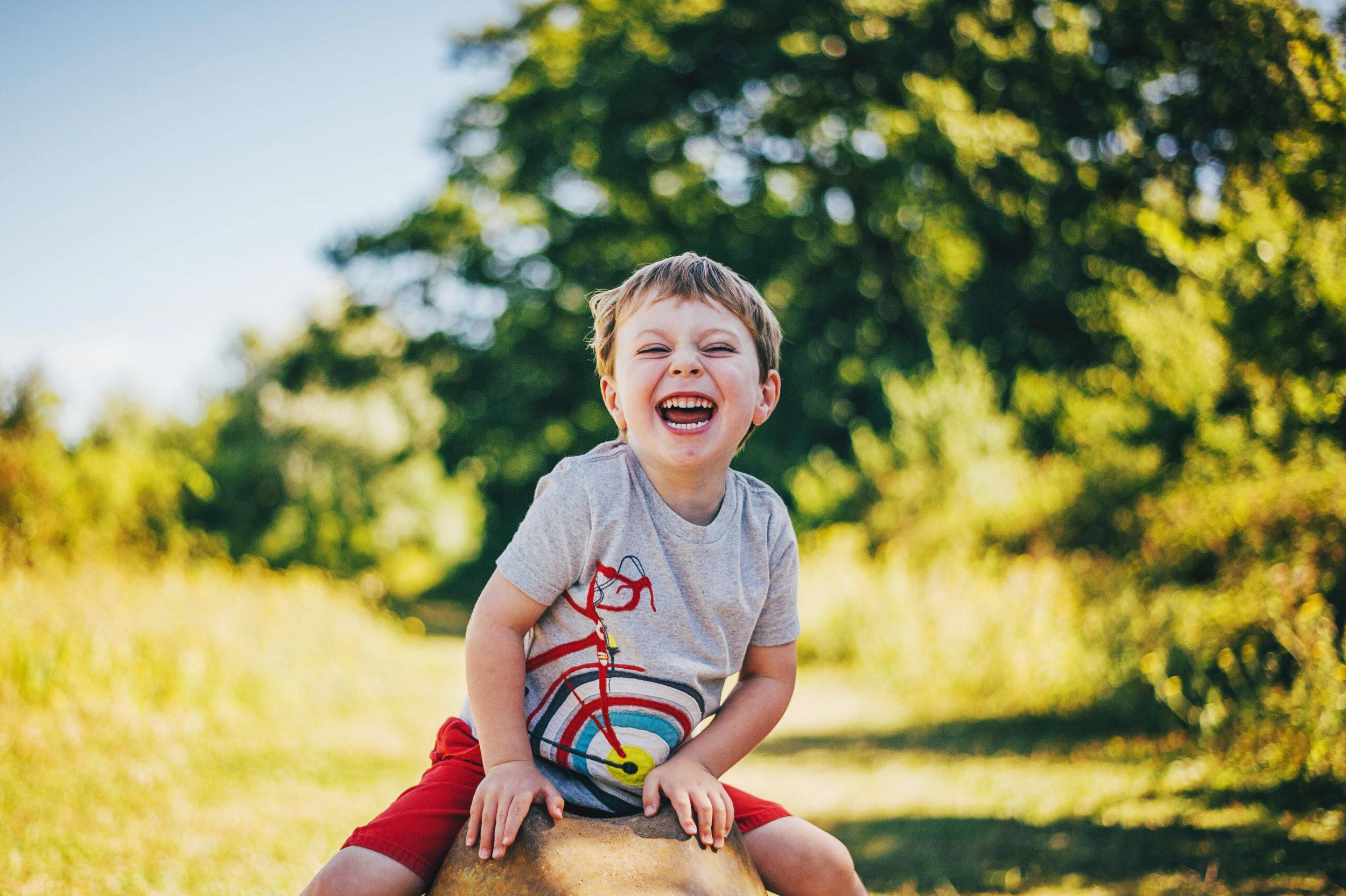 Little boy laughs in sunny park Essex UK Documentary Natural Portrait Photographer