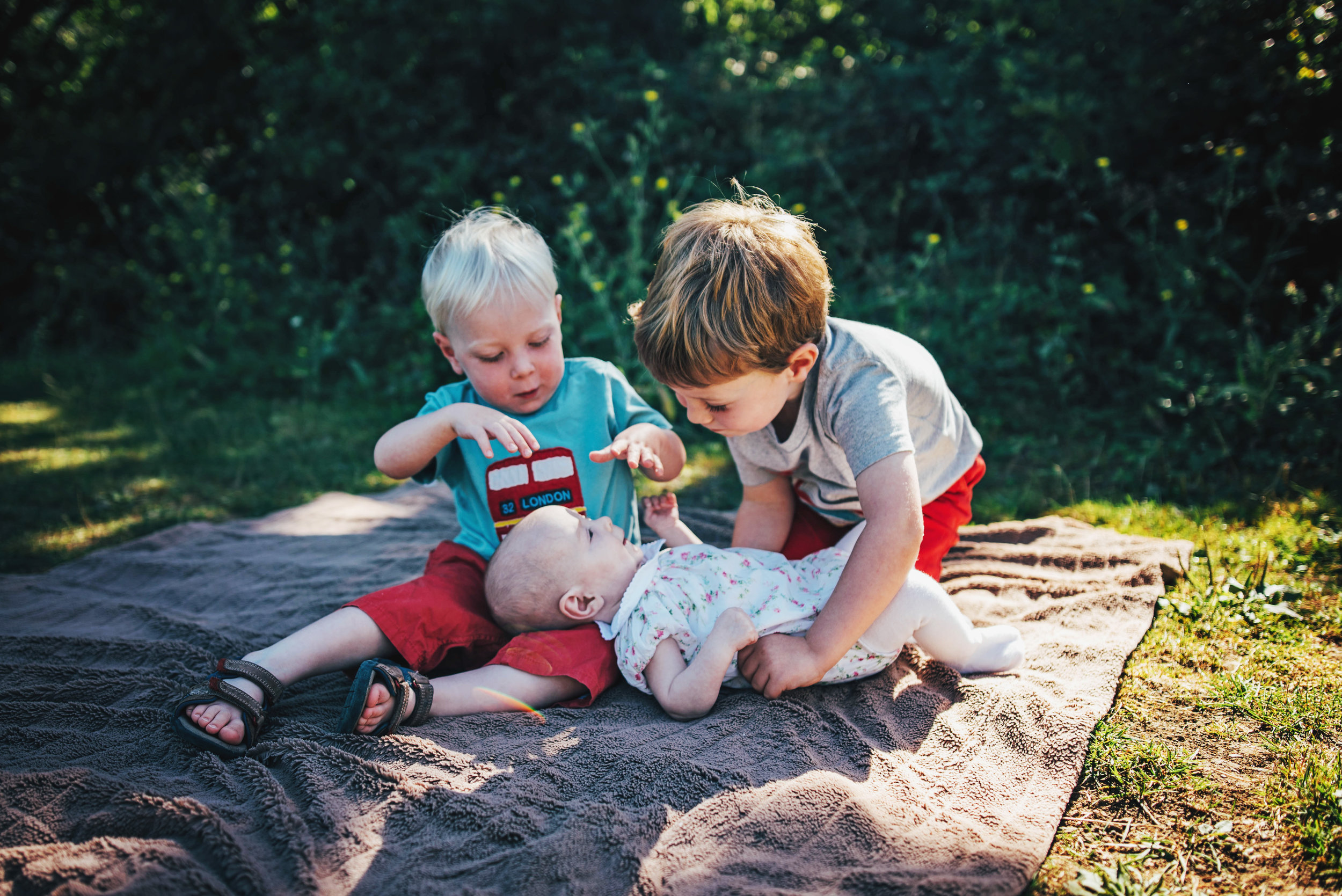 Two big brothers hug baby sister in sunny park Essex UK Natural Documentary Portrait Photographer