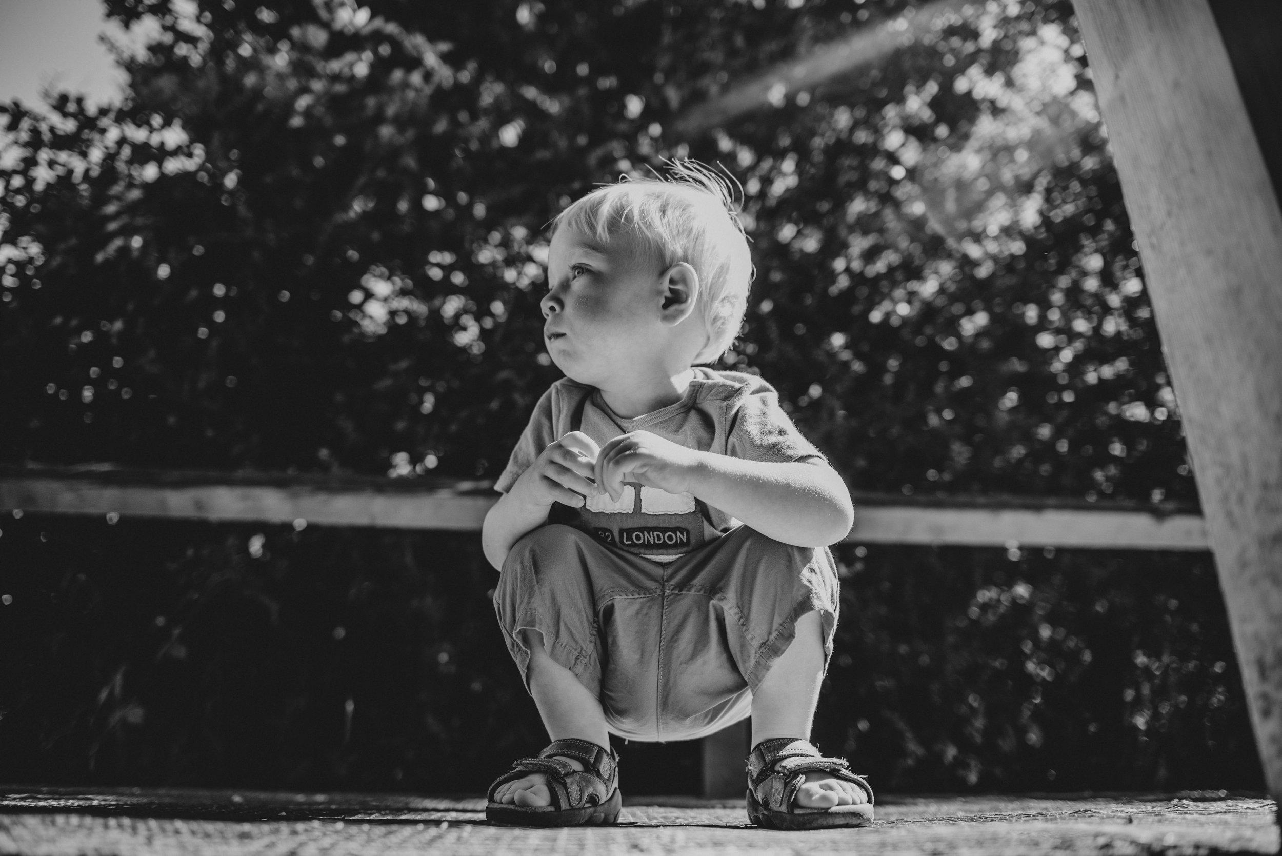 Little boy crouches on bridge sunny park Essex UK Natural Documentary Portrait Photographer