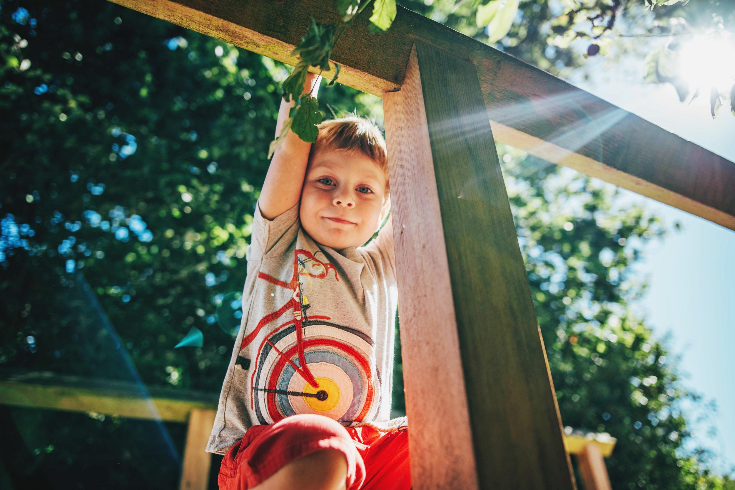 Boy crouches on bridge in sunny park Essex UK Natural Documentary Portrait Photographer