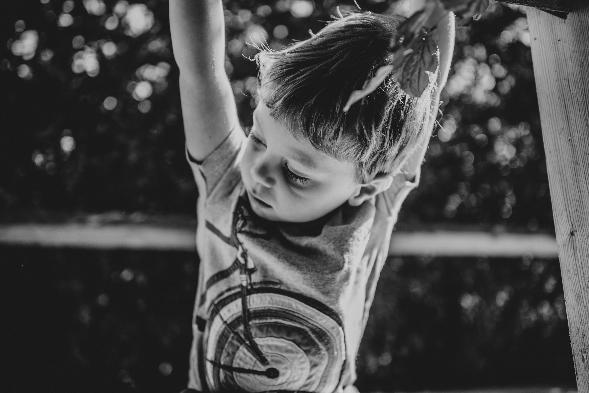 Little boy crouches on bridge Natural Essex UK Documentary Portrait Photographer