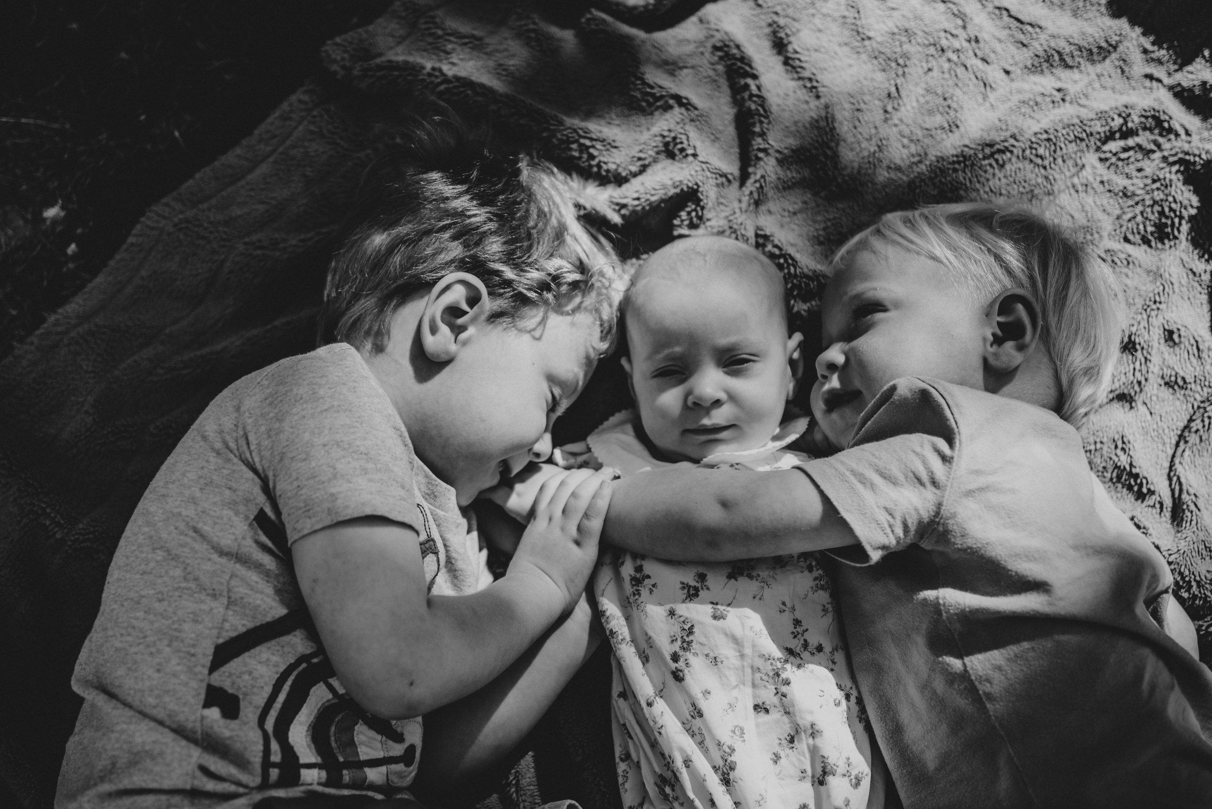 Big brothers hug baby sister Natural Documentary Portrait Photographer Essex UK