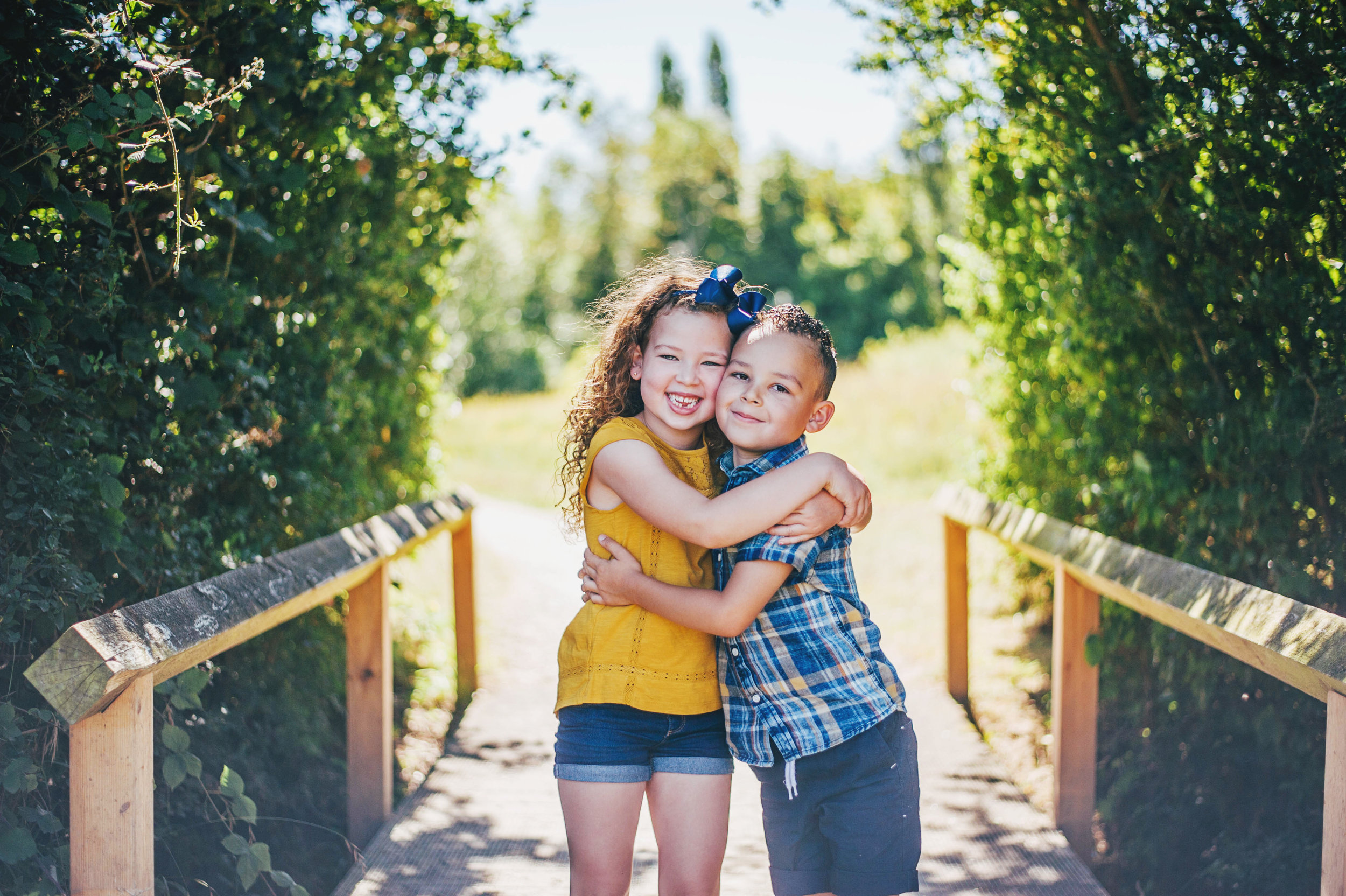 Brother and Sister hug on a bridge Natural Essex UK Documentary Portrait Photographer
