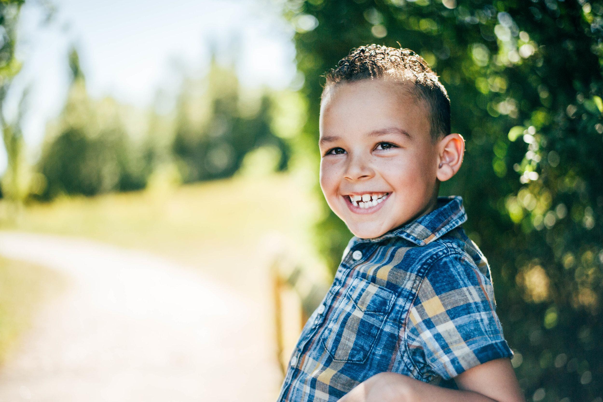 Boy smiles on bridge Essex UK Natural Documentary Portrait Photographer