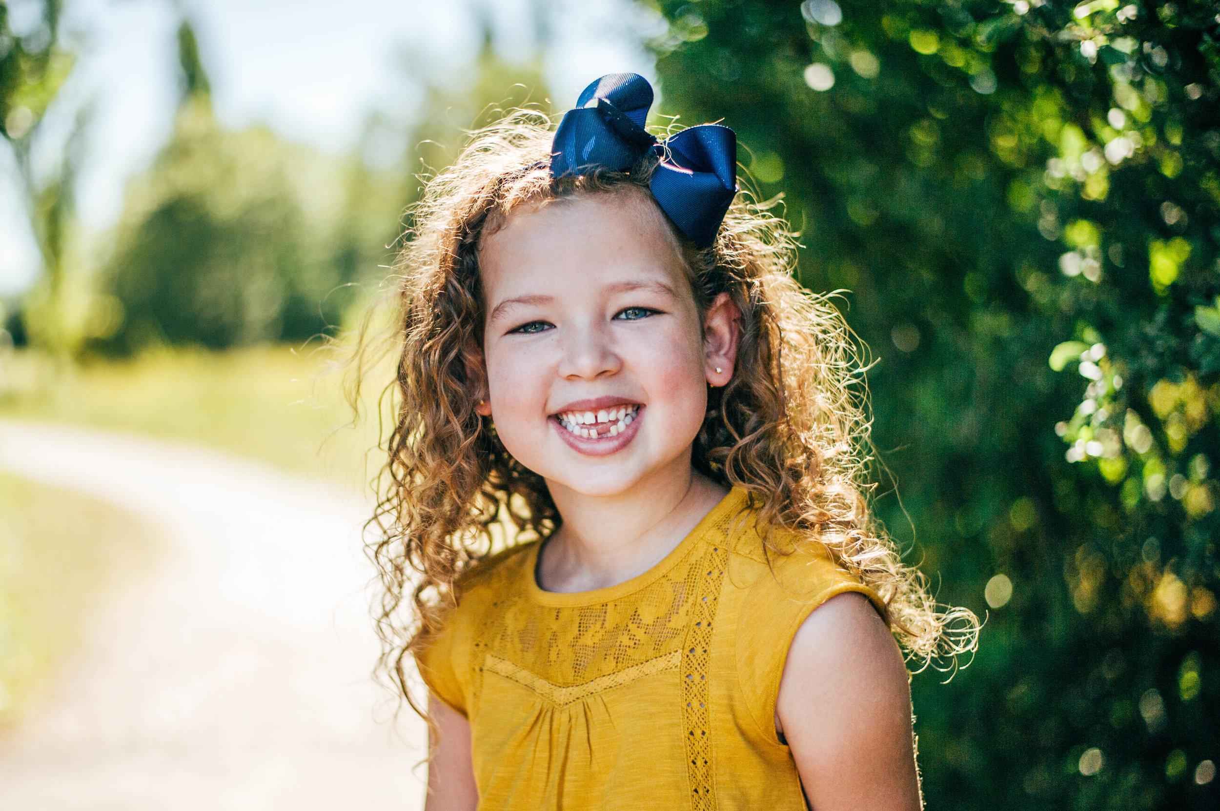 Little girl smiles on bridge Essex UK Natural Documentary Portrait Photographer