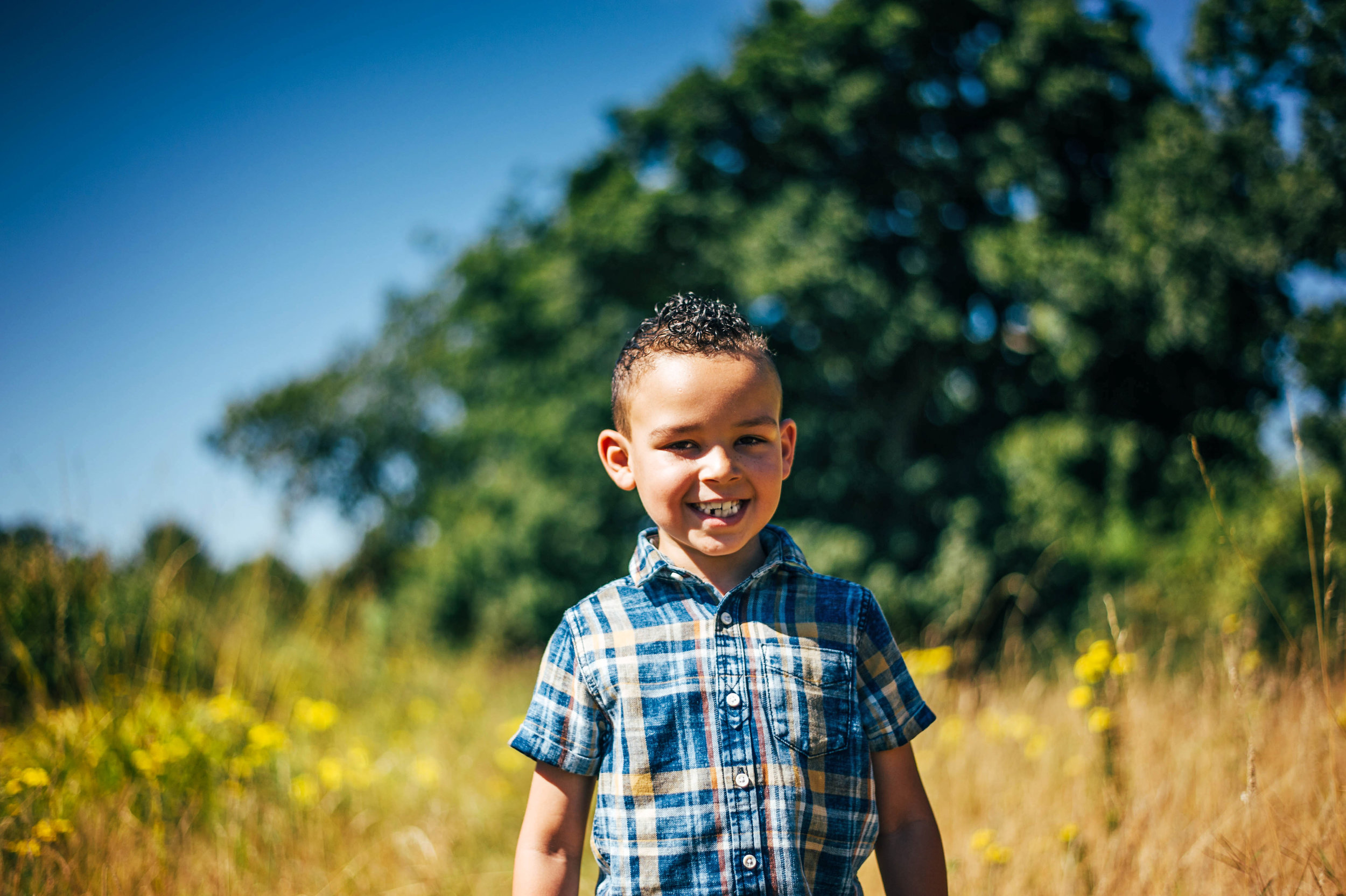 Boy smiles in long grass Essex UK Natural Documentary Portrait Photographer