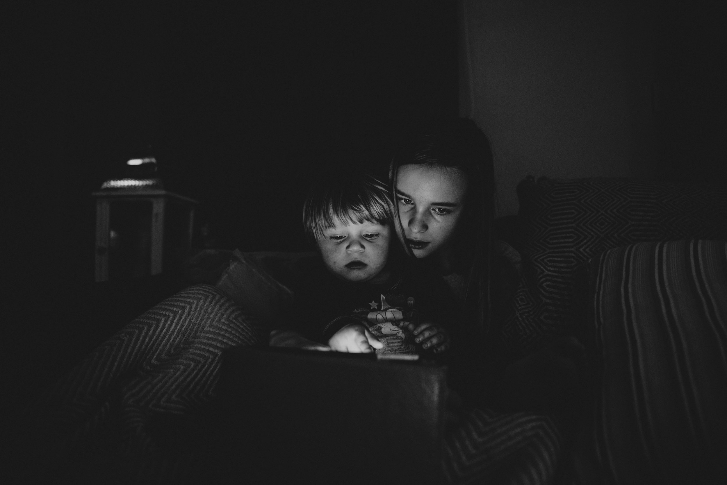 Girl and baby boy look at iPad in the dark Essex UK Documentary Photographer