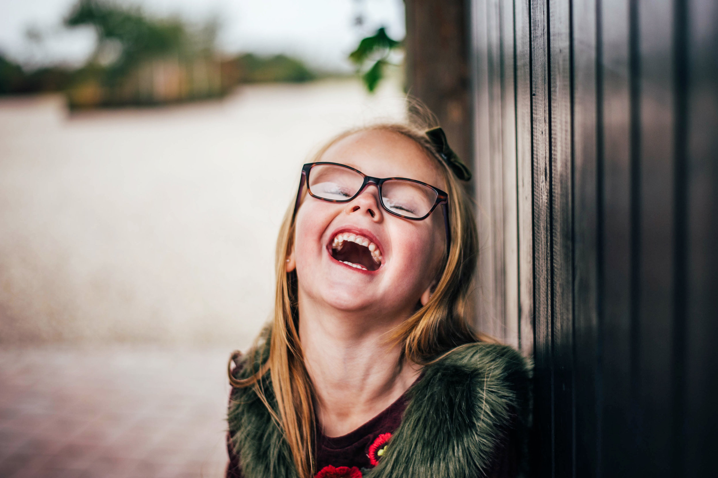 Young girl in glasses laughs Essex UK Family Childhood Portrait Documentary Photographer